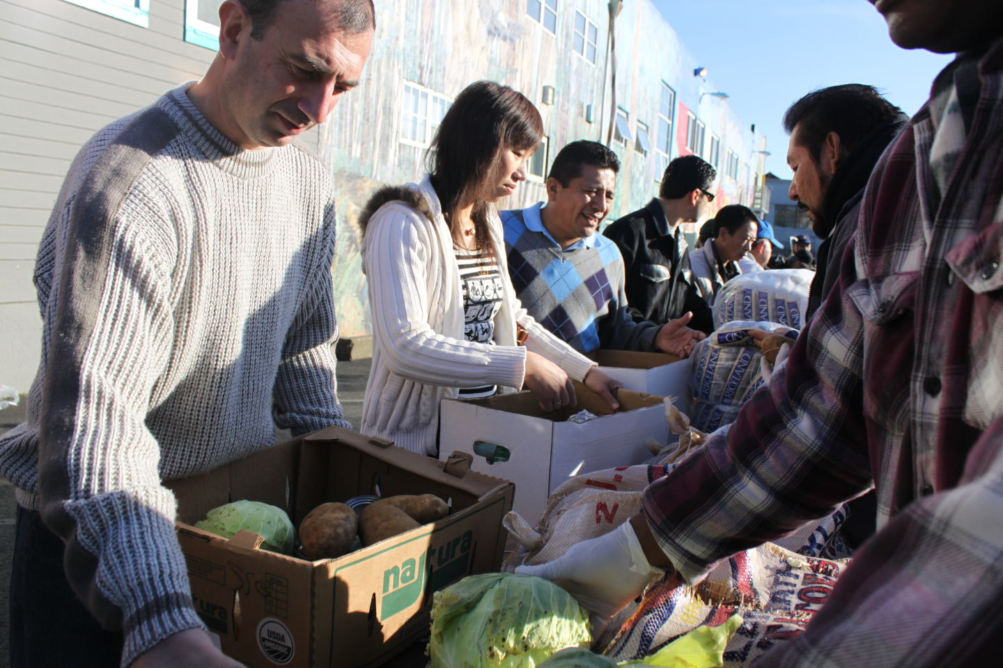Volunteers help distribute food to participants at one of the SF-Marin Food Bank's pantries