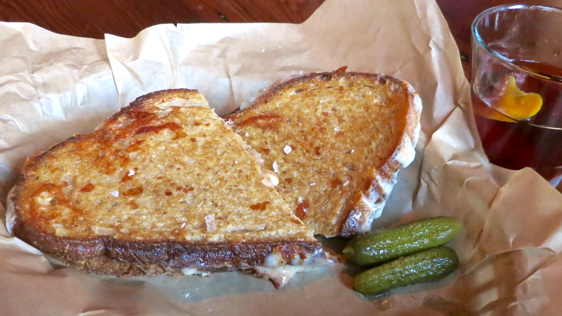 "The Lodge's signature grilled cheese sandwich with bacon chutney and their ""Black Rider"" cocktail."