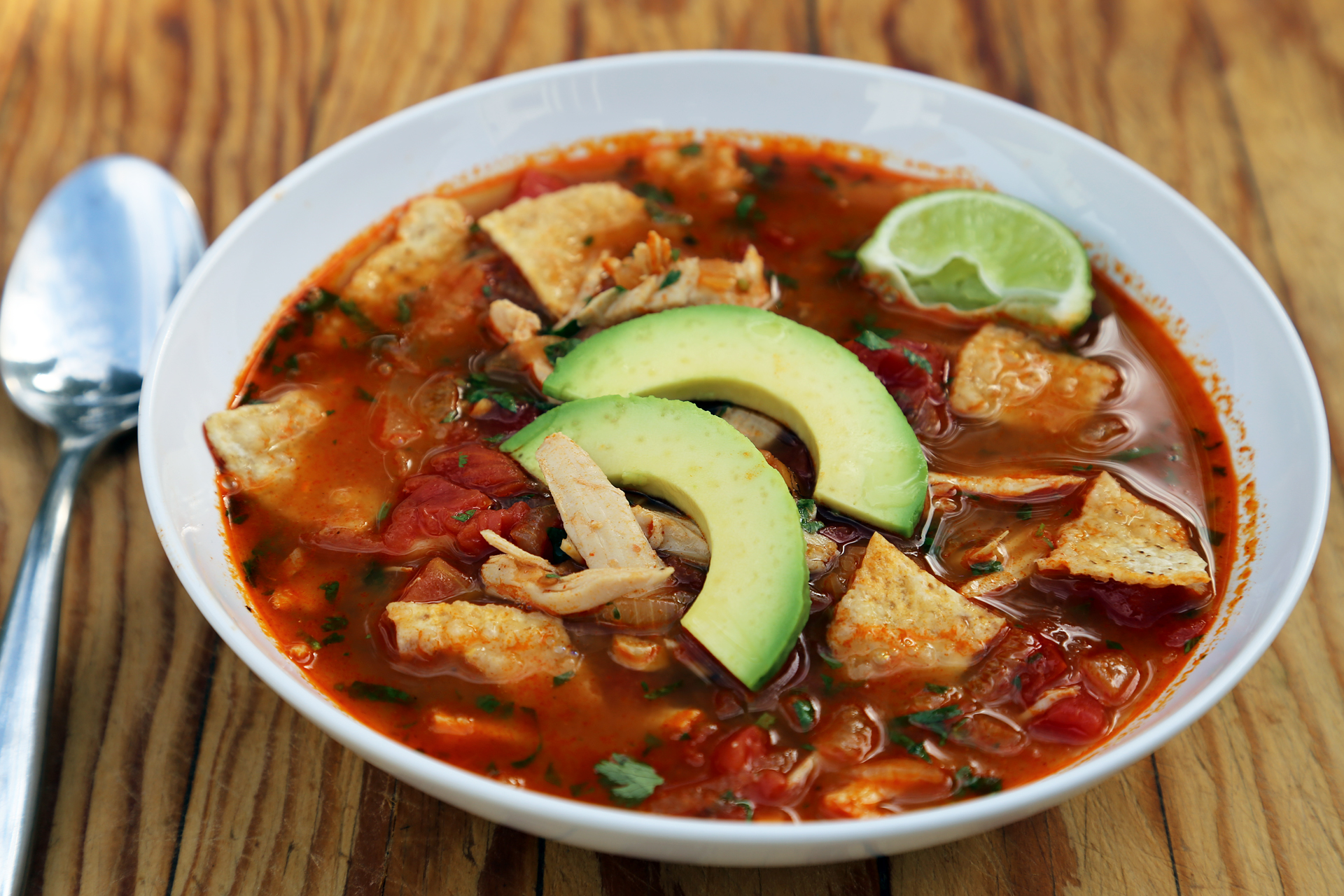 Serve bowlfuls, garnished with plenty of avocado, queso fresco, crushed tortilla chips and lime wedges on the side.