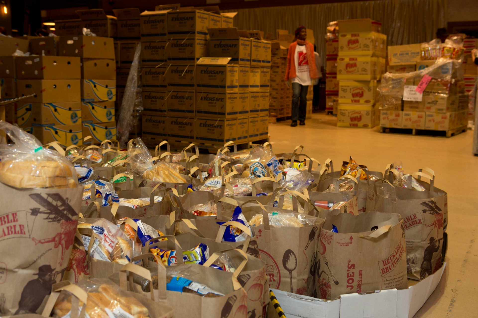 Volunteers prepare bags of food for a PHC event.
