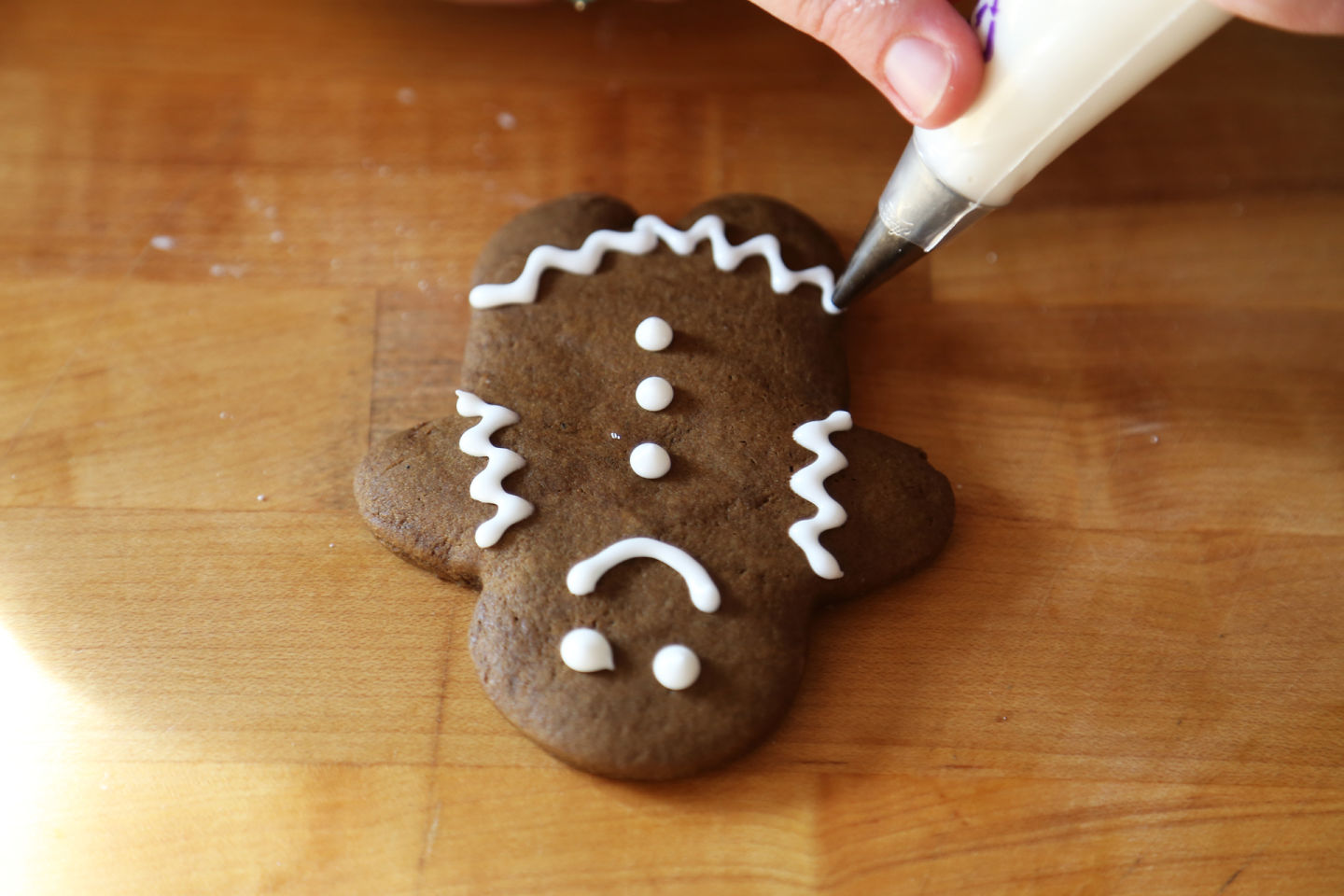 Decorating a gingerbread person with royal icing.  Wendy Goodfriend