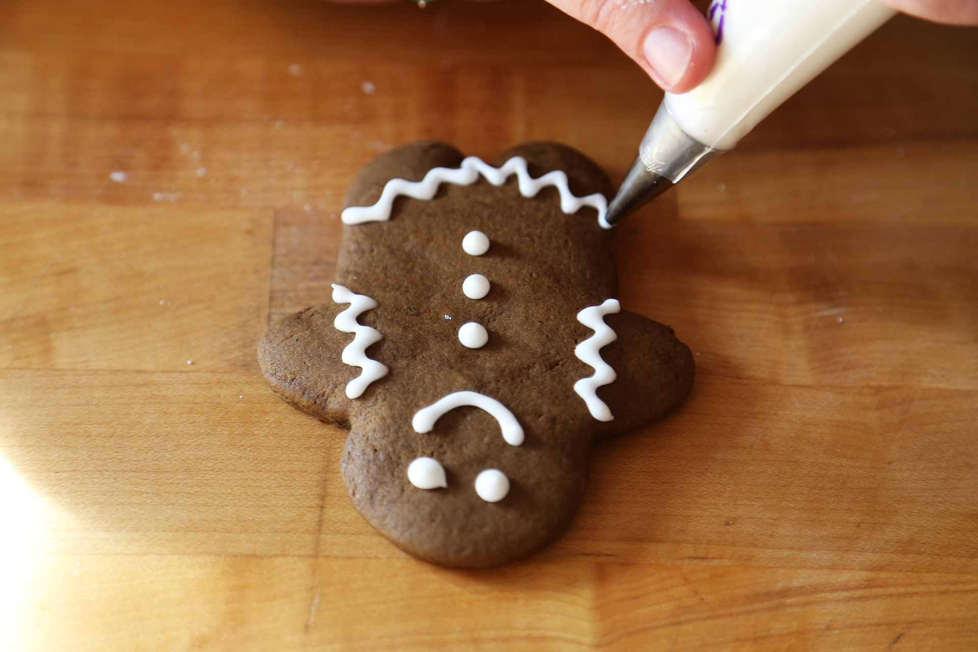 Decorating a gingerbread person with royal icing.