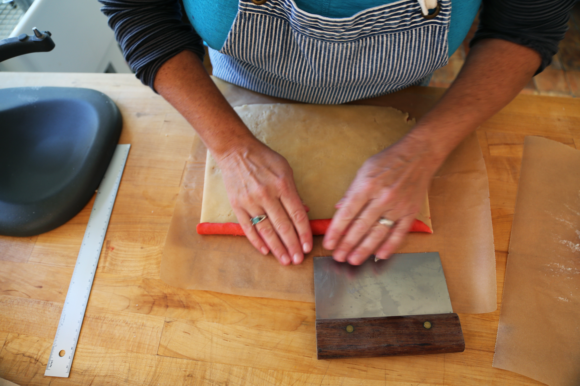 Using the paper to help, roll up the dough lengthwise into a tight log.