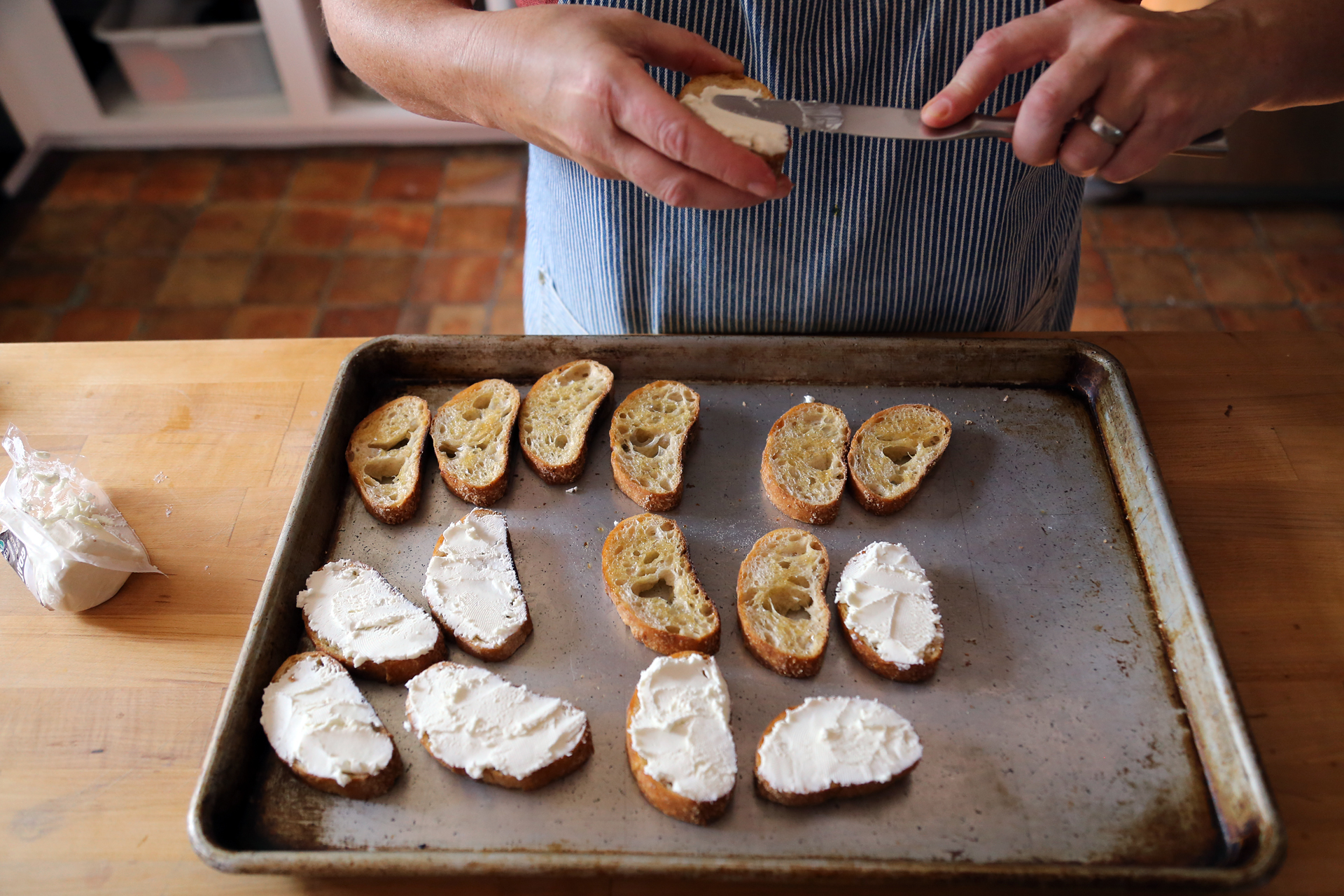 Spread each crostini thickly with goat cheese.