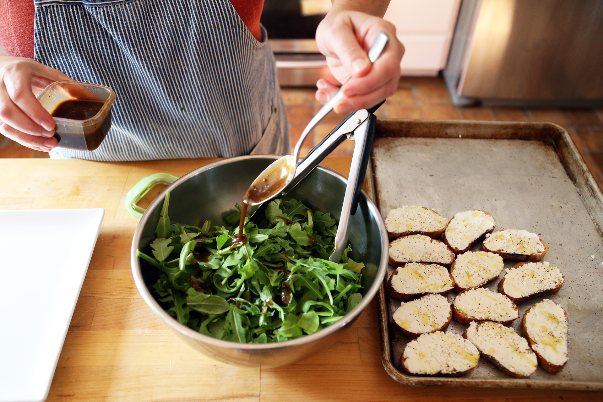 In a mixing bowl, toss the arugula with about 2 tbsp of the vinaigrette.