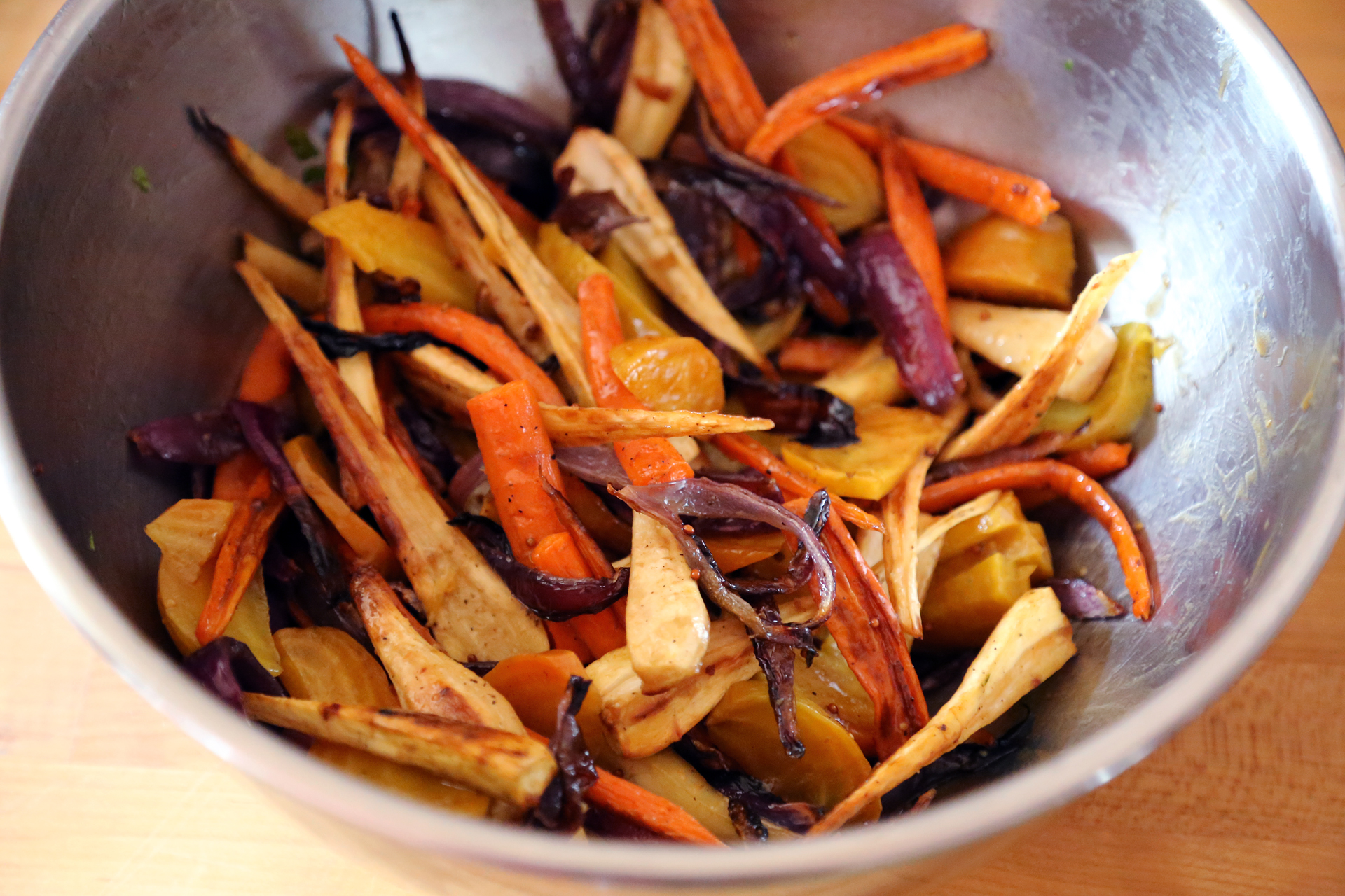 Add the roasted vegetables to the mixing bowl and toss with 2 tbsp vinaigrette.