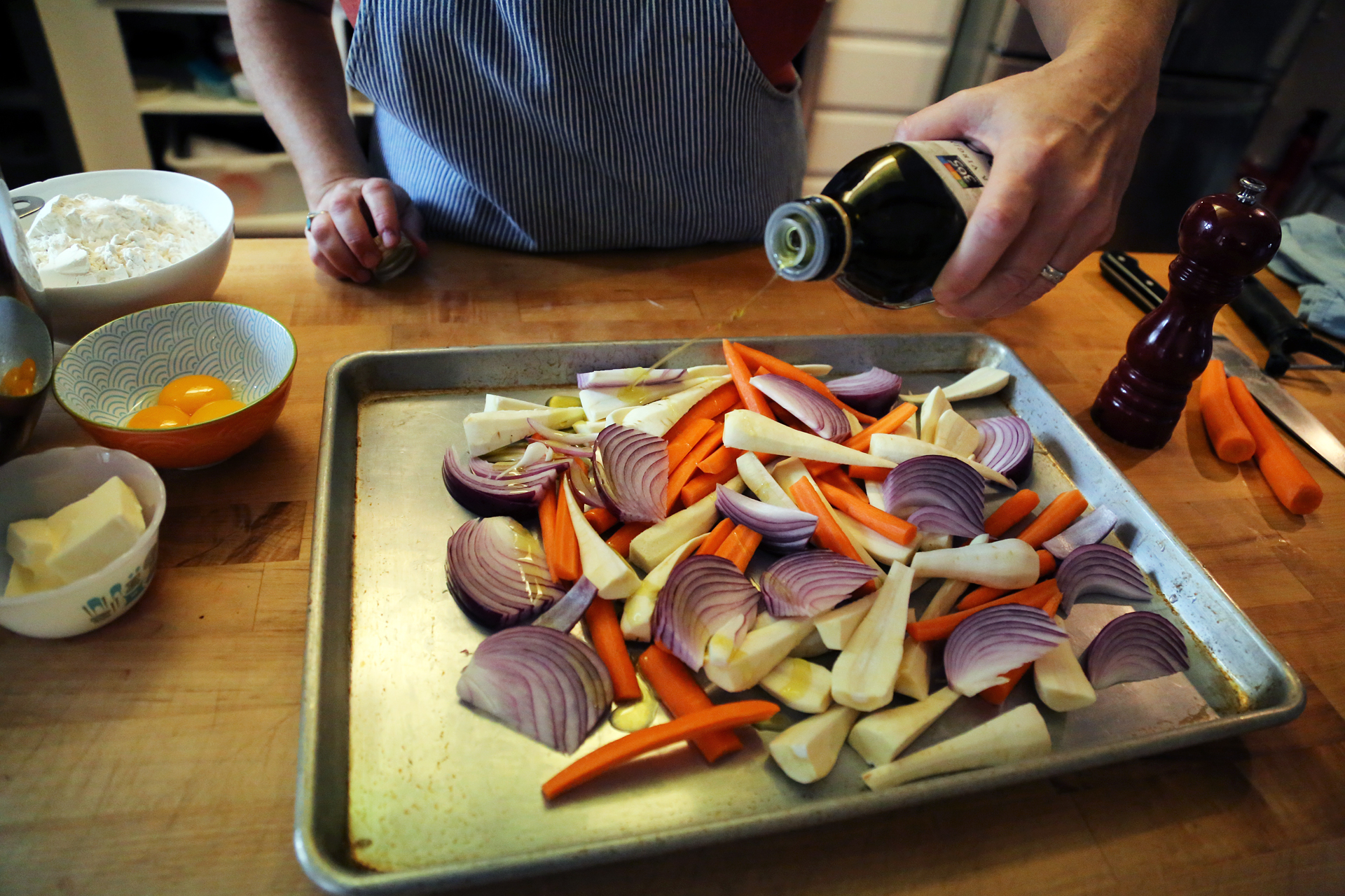 Cut the onion into wedges. Add the vegetables to a large rimmed baking sheet, drizzle with olive oil and toss to coat.