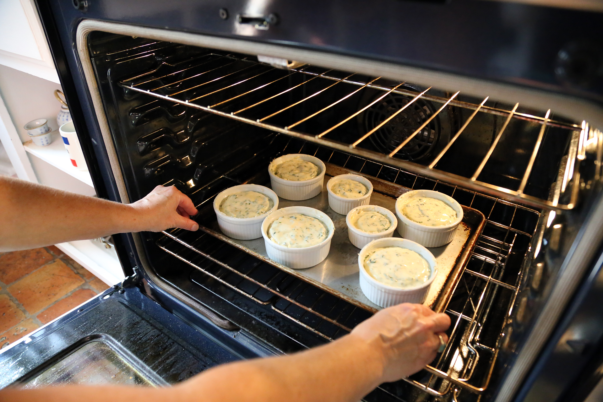 Bake until the soufflés are puffed and browned and the center still jiggles when the dish is gently shaken, about 20 minutes. Do not open the oven door during cooking.