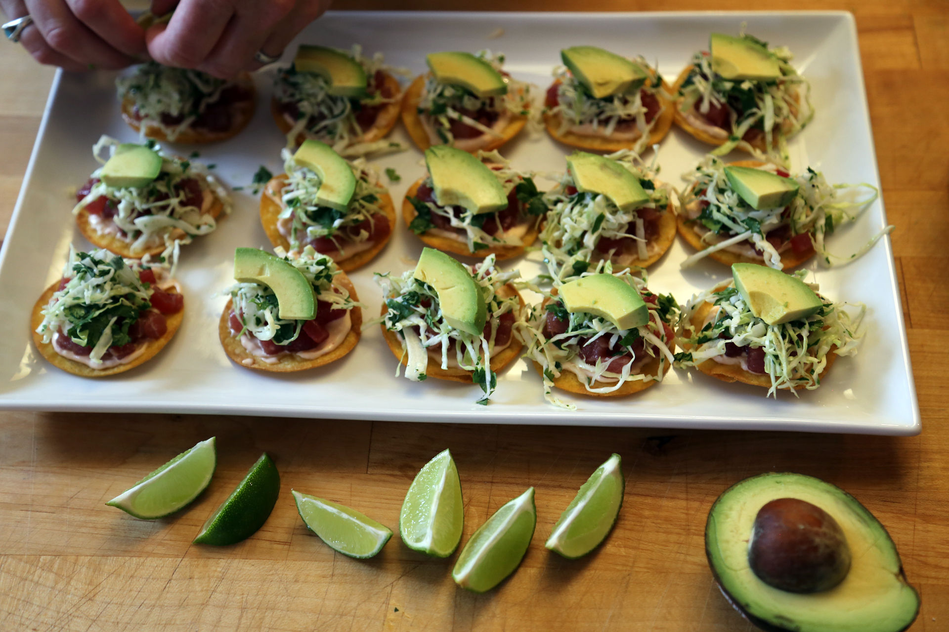 Add a slice of avocado to each tostada. Serve with the lime wedges alongside for squeezing.