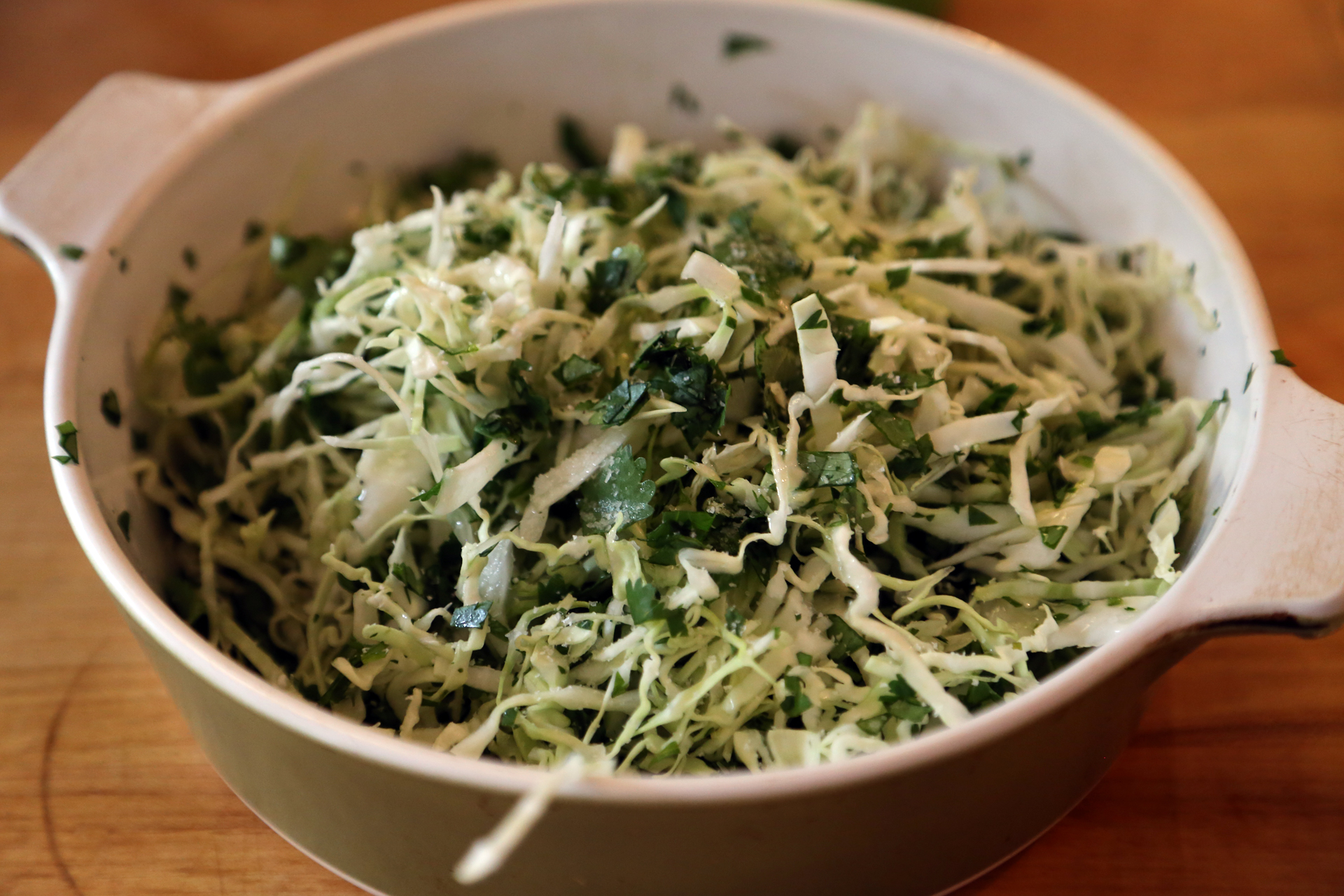 In a third bowl, stir together the cabbage and cilantro, then sprinkle with the vinegar and season with salt and pepper.