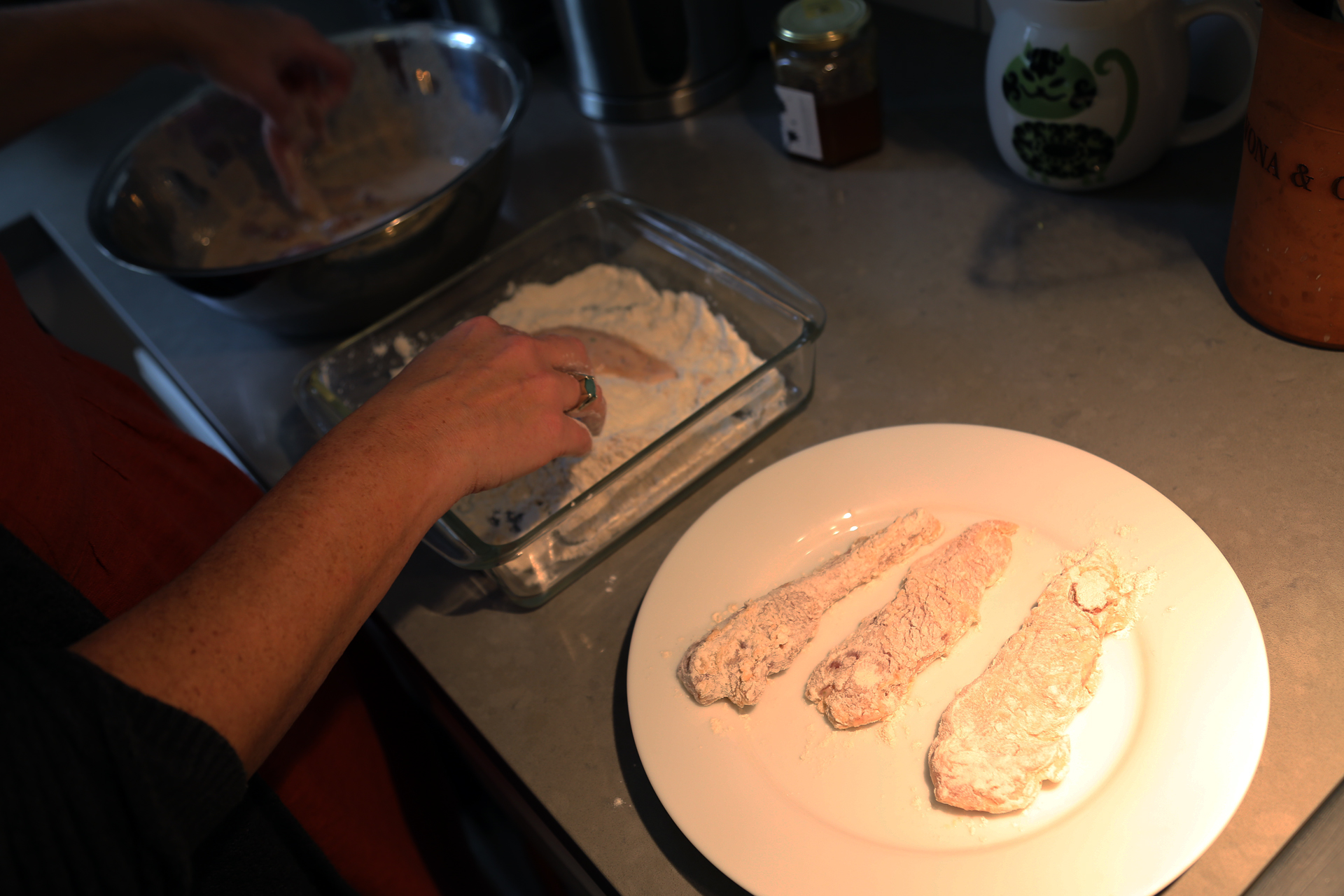 Pick up a chicken strip and let the buttermilk mixture drip off (but leave some of it coating the chicken). Dredge each strip in the flour mixture, coating it evenly, then set it aside on a plate.