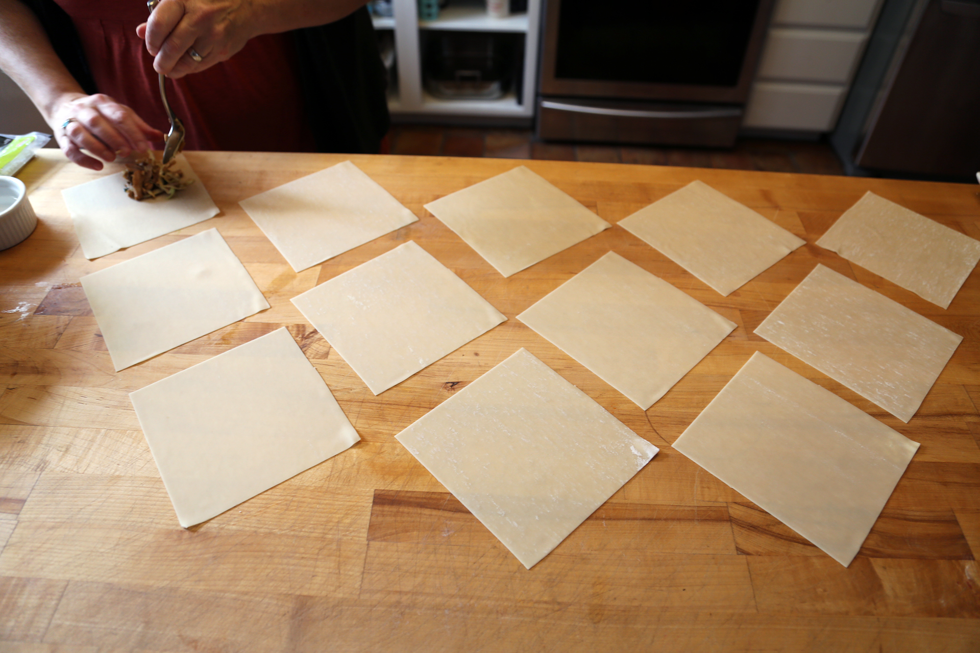 Spread out the egg roll wrappers on a work surface. Divide the mixture between the wrappers, placing the filling near one corner.