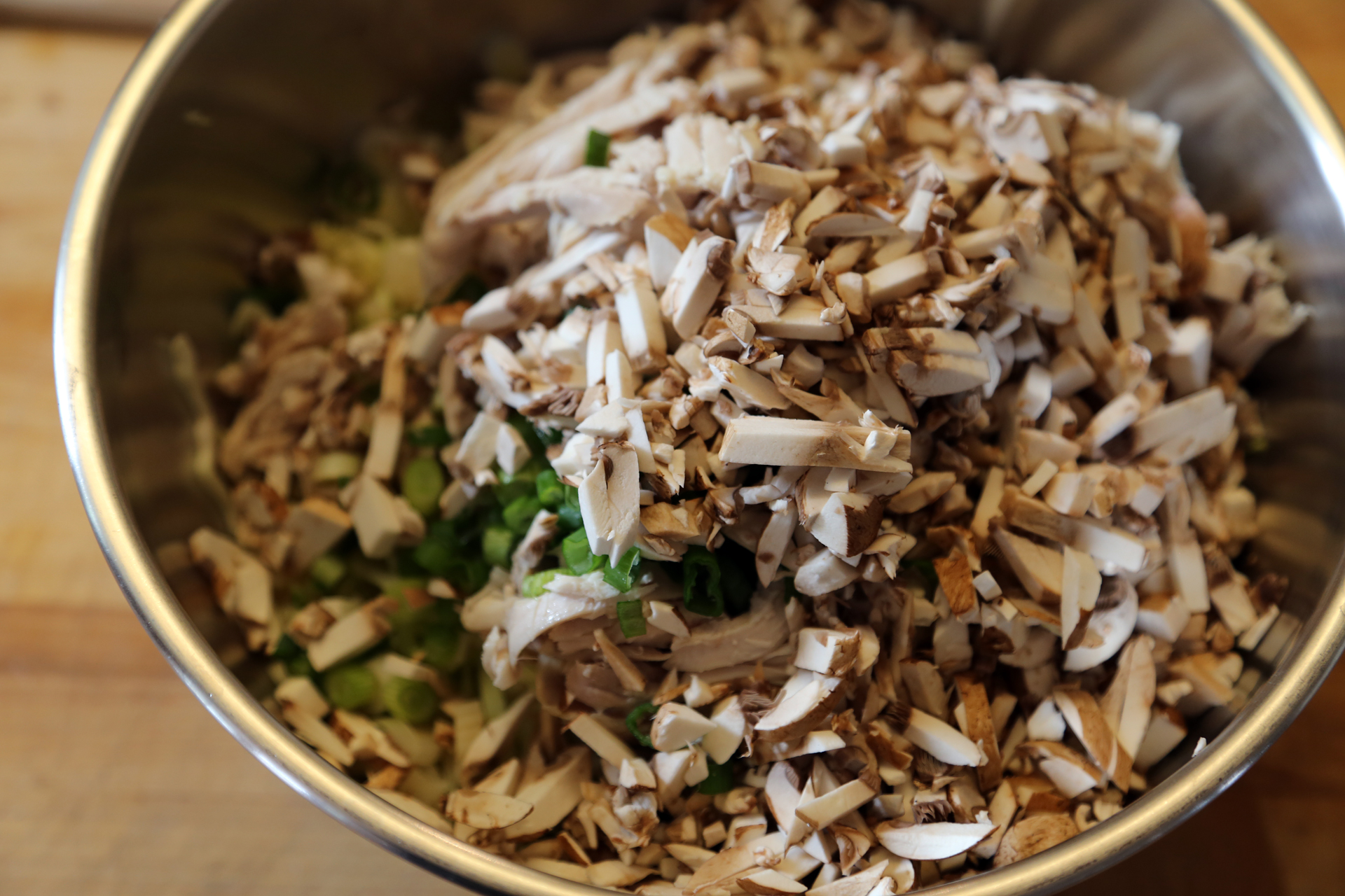 In a large mixing bowl, toss together the shredded chicken, cabbage, mushrooms, green onions, and water chestnuts.