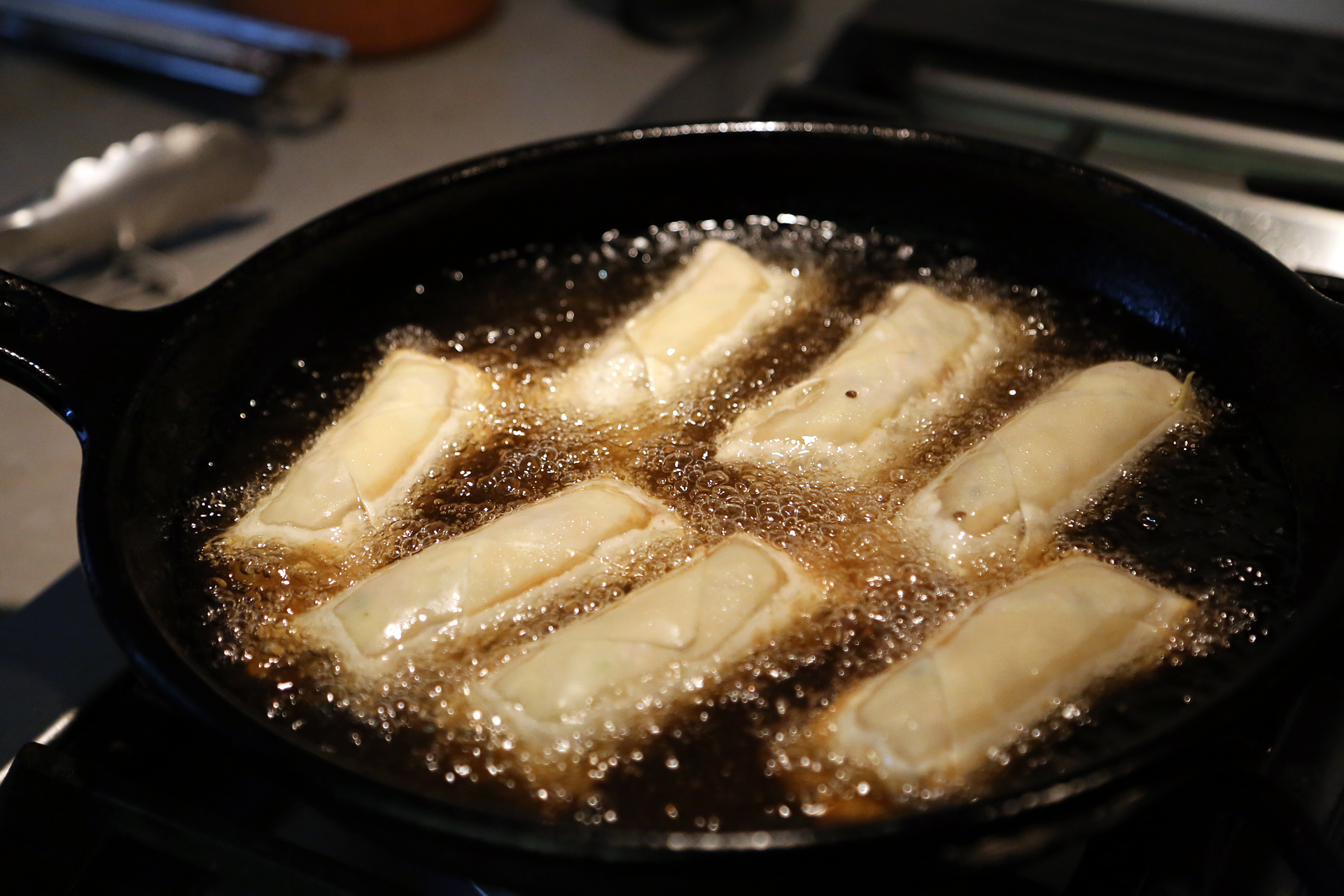 In a large frying pan over medium-high heat, warm 1/3 inch of the oil until shimmering. Fry the egg rolls in batches.