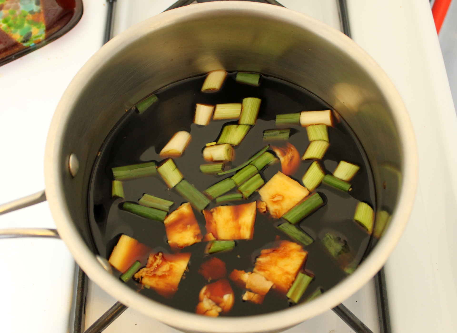 To make shoyu tare, combine soy sauce, sake, scallions, ginger, mirin, and garlic in a medium saucepan. Bring to a boil over high heat. Remove from the heat and let cool to room temperature. Strain and discard solids.