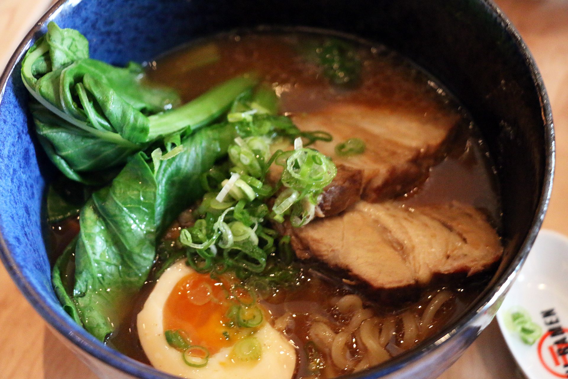 Shoyu ramen with pork cha siu, bamboo shoots, yu choi, green onion, and jidori egg.