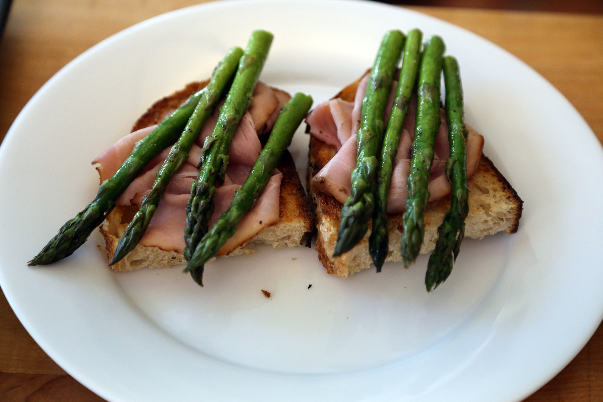 Divide the toast between warmed individual plates, using 1 or 2 slices per plate. Top each slice with a slice of ham, then divide the asparagus between the toasts.
