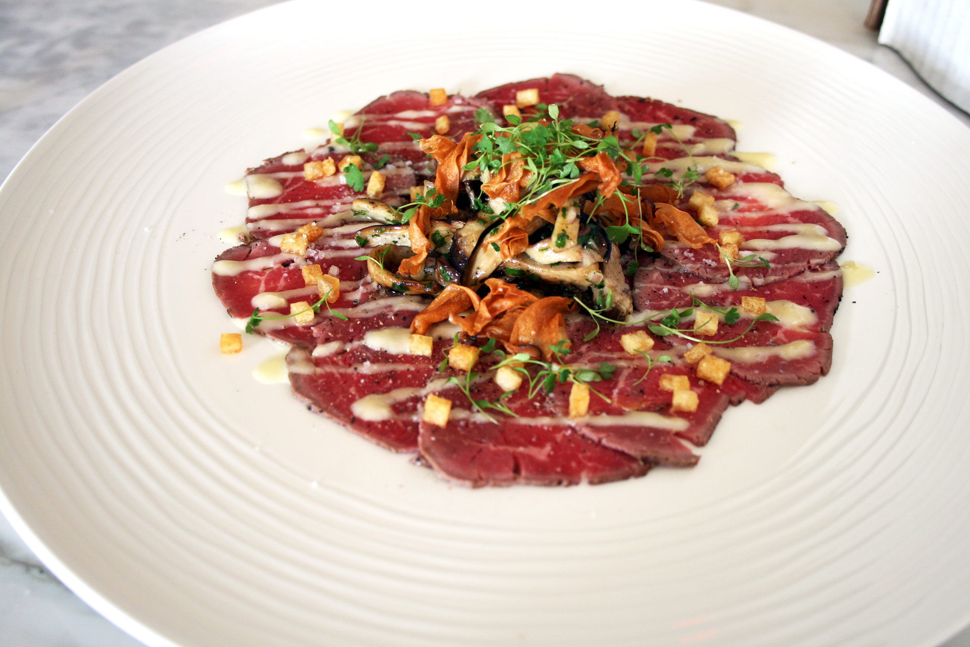 Beef Carpaccio — meltingly fatty, perfectly sliced and topped with sauteed trumpet mushrooms.