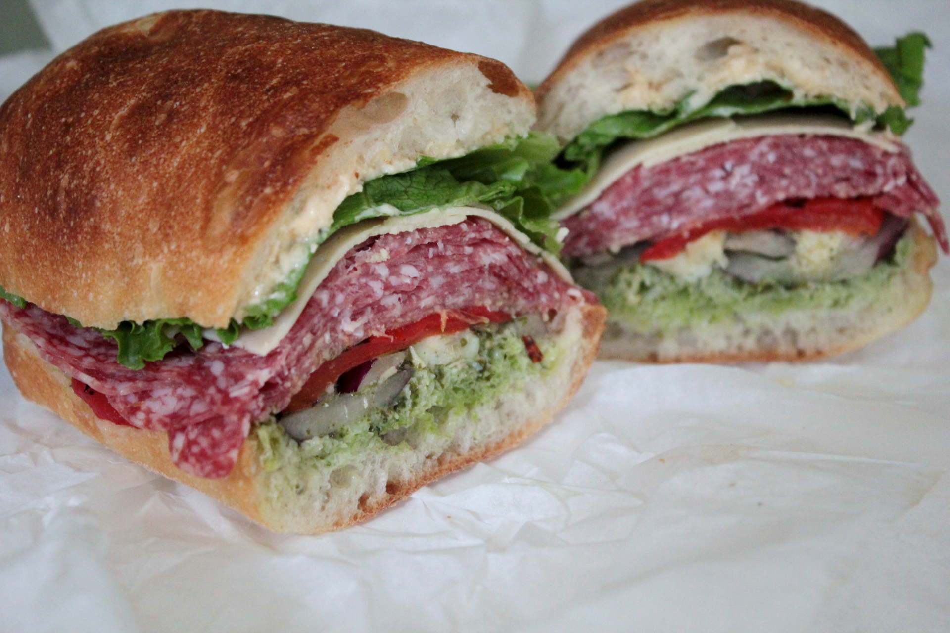 The Woodside Grand Champion features salami, artichoke hearts, red onions, red bell peppers, asiago and pesto.