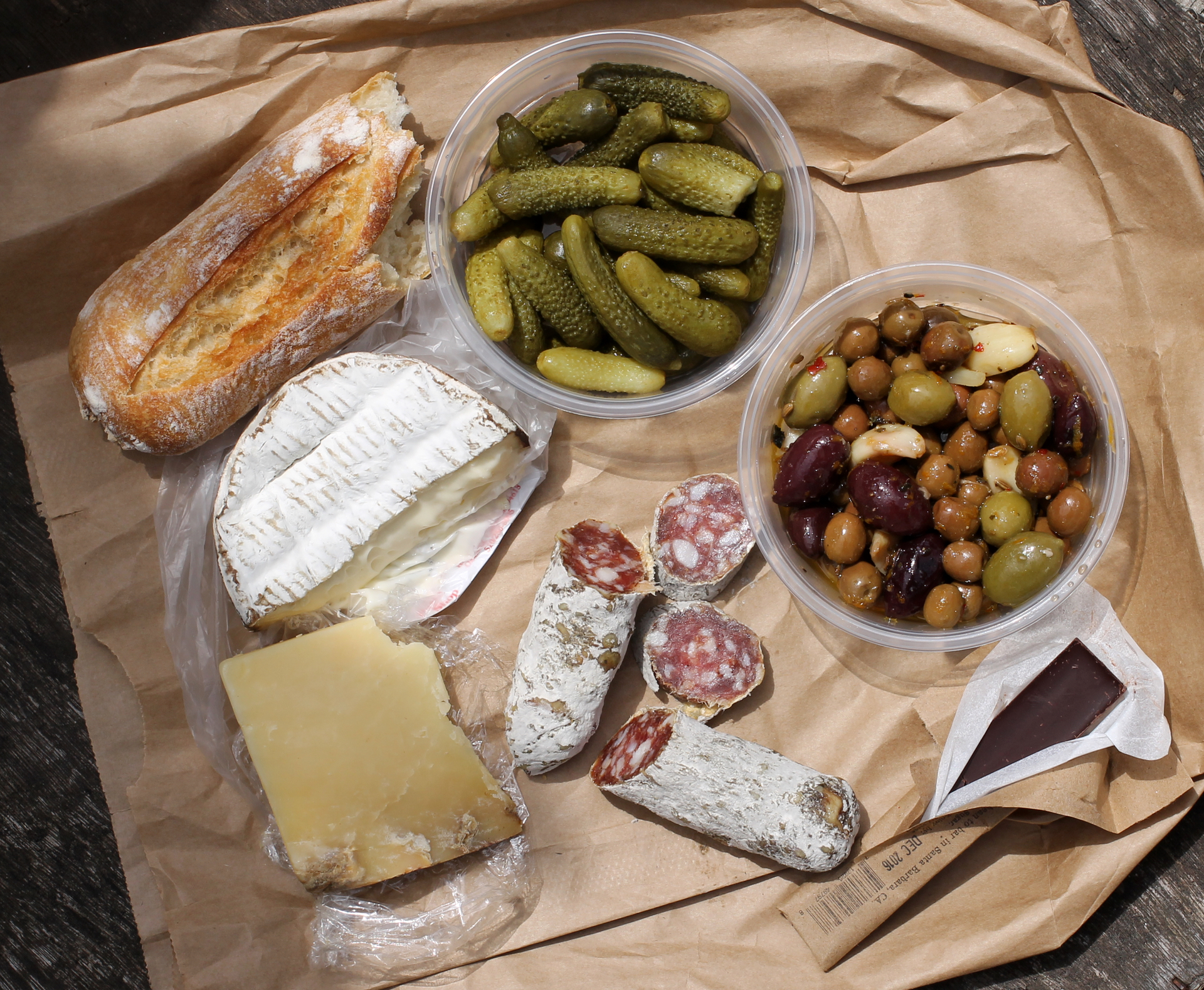 From top left, moving clockwise: Semifreddi's baguette, cornichon, mixed olives, Twenty-four Blackbirds chocolate, Olympia Provisions sopressata, Montgomery's Farmhouse cheddar, and Jasper Hill Harbison, all from The Pasta Shop.