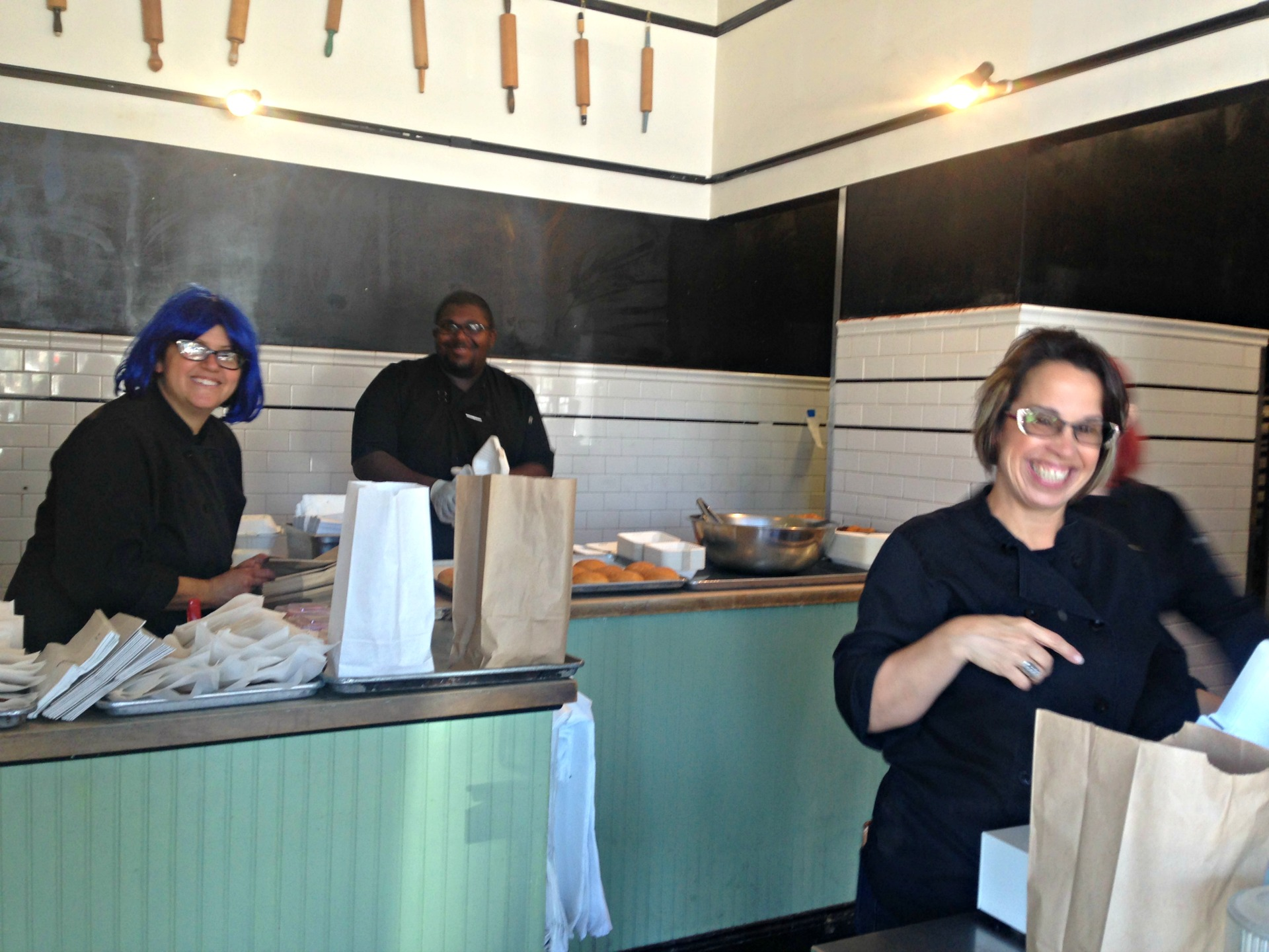 Bakesale Betty's owner blue-wigged Alison Barakat and cheerful workers.