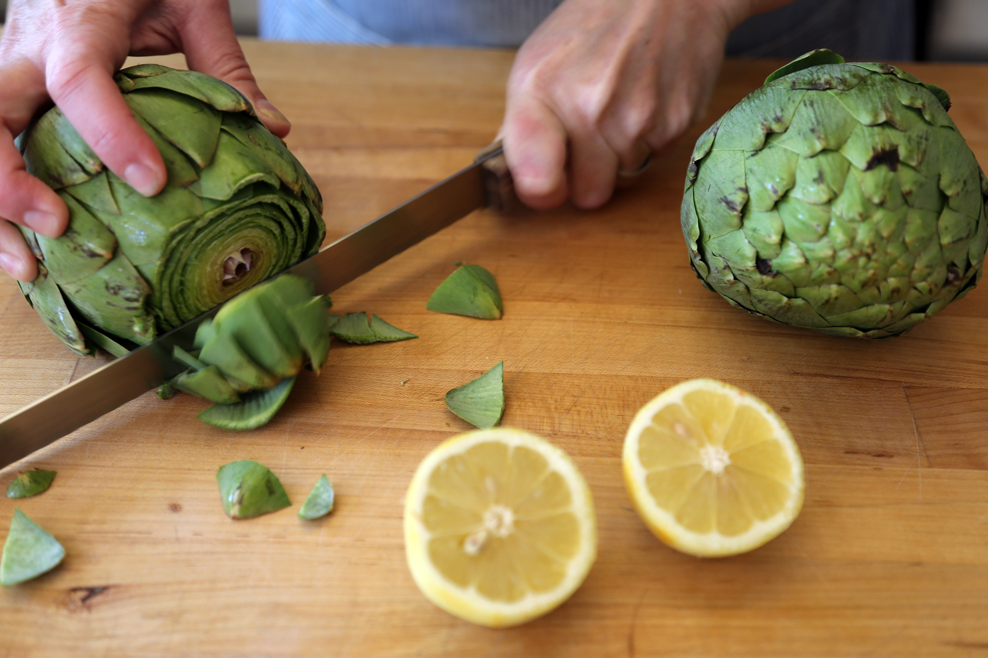 To prepare the artichokes, using a serrated knife, cut off the top 1-inch of the artichoke.
