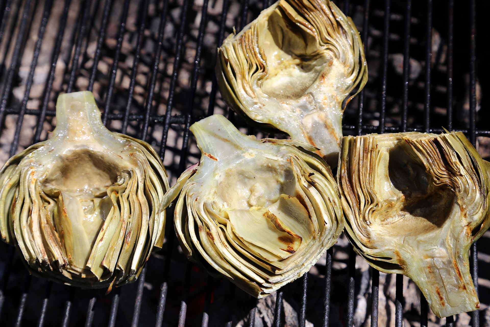 Brush the grill grate with oil. Brush the artichokes all over with the oil and season with salt. Grill, turning occasionally.