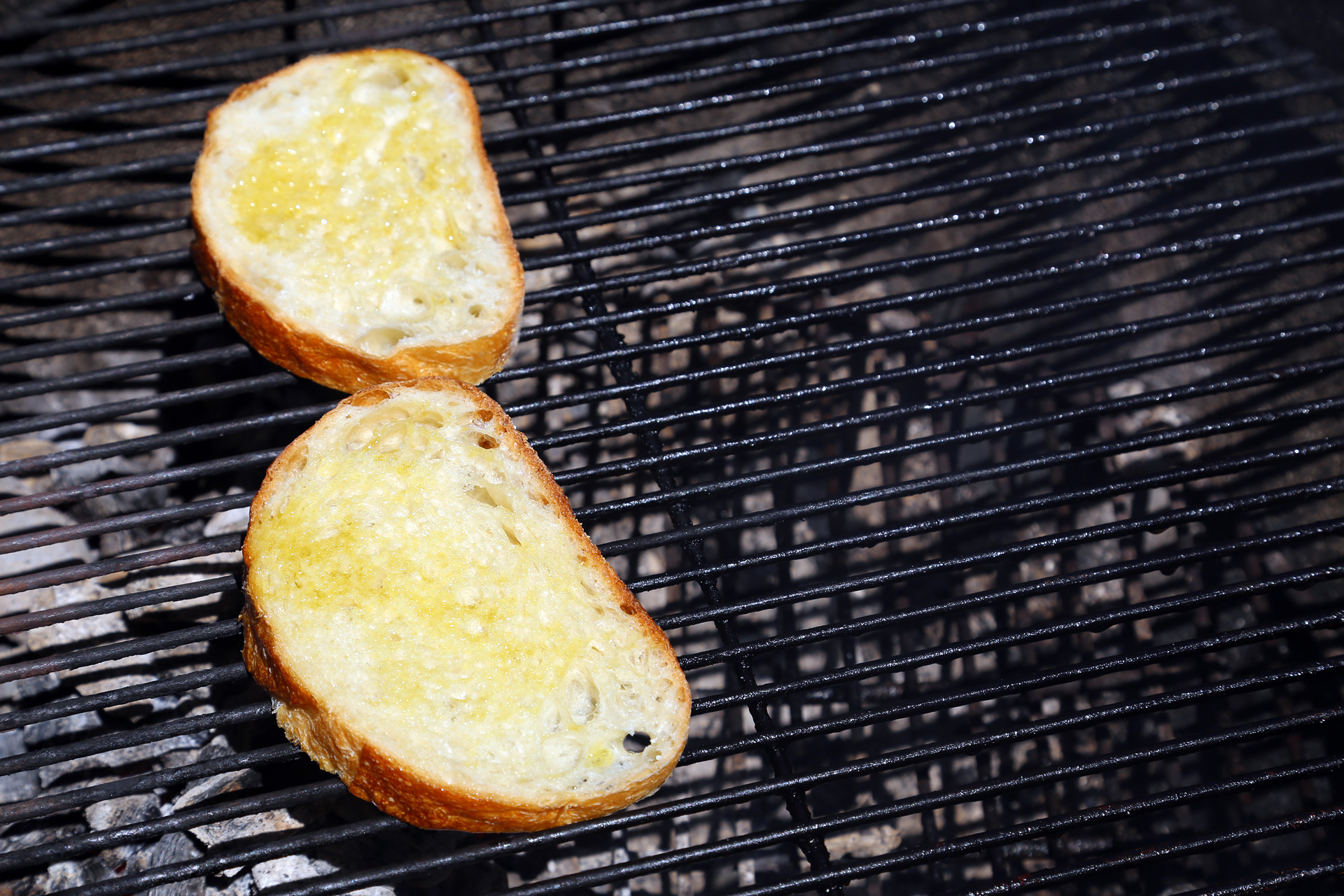 Brush both sides of each bread slice with a little olive oil then place over the fire, turning once, until the bread is toasted and nicely grill-marked.