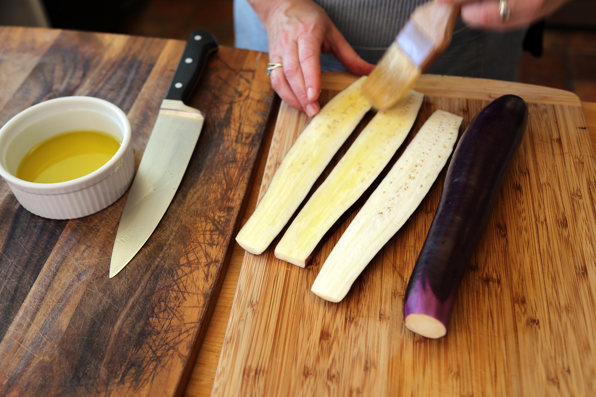 Trim the eggplant and slice it lengthwise into 1/2-inch pieces. Brush it with olive oil.
