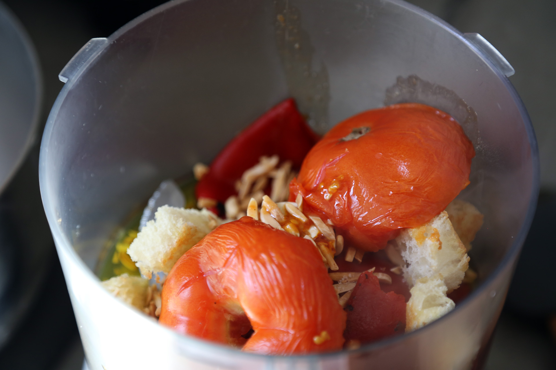 Continue to roast the tomato and garlic for another 10 minutes. Remove the tomato peel and discard. Transfer the tomato and garlic to the food processor.