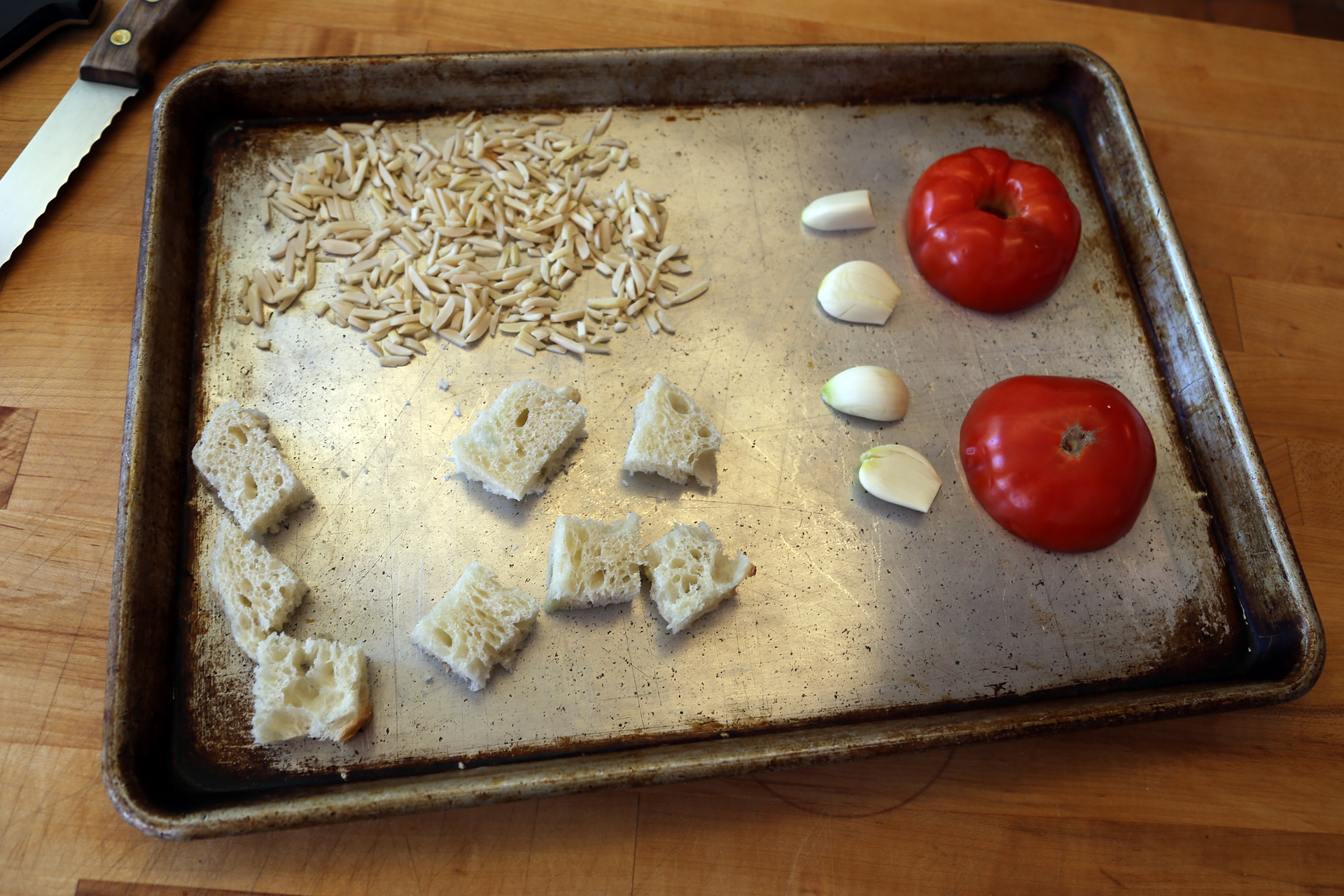 Place the tomato, cut side down on one side of a rimmed baking sheet and arrange the garlic next to it. On the other side, add the bread and almonds.