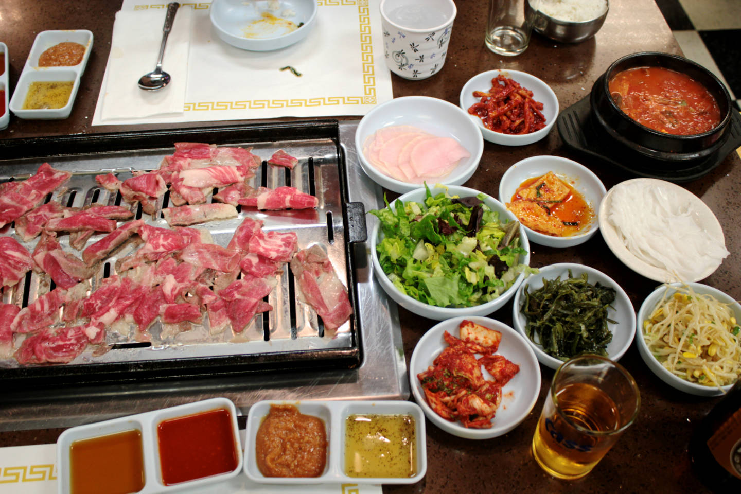 The banchan selections and thinly sliced beef cooking on the grill at To Bang.  Jeff Cianci