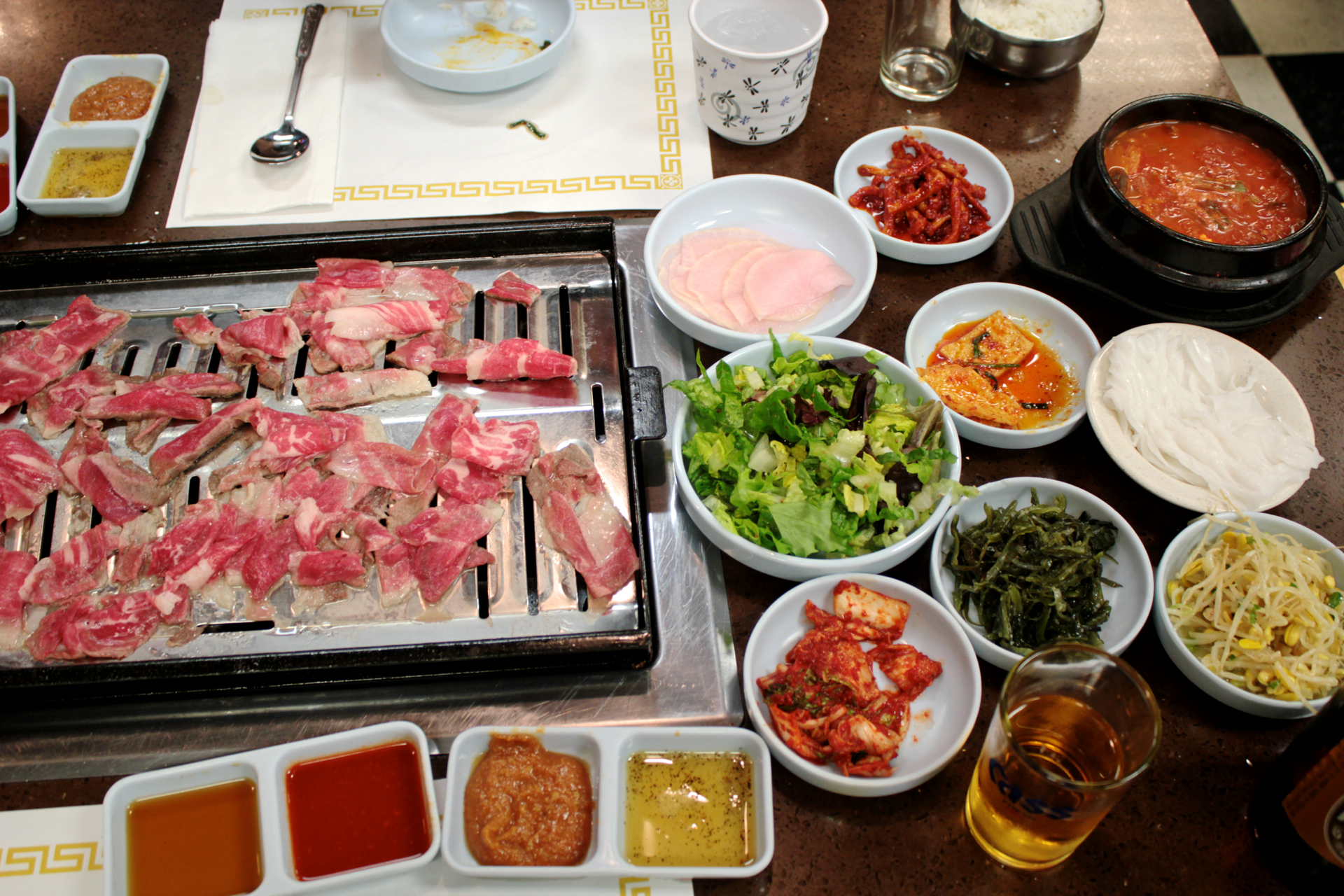 The banchan selections and thinly sliced beef cooking on the grill at To Bang.