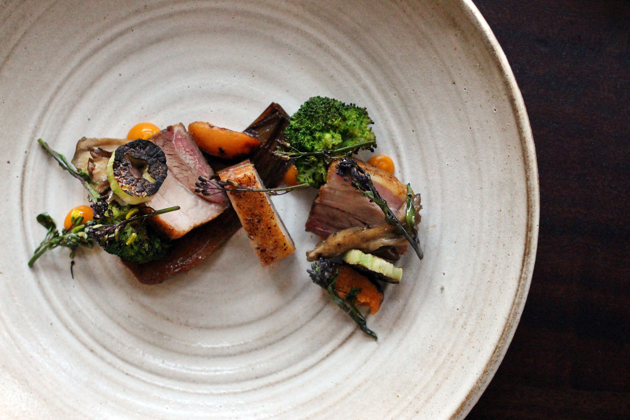 Pork Belly with Charred Broccoli, Maitake, Aztec Apricot, Sprouts, and Spring Onion at The Alembic