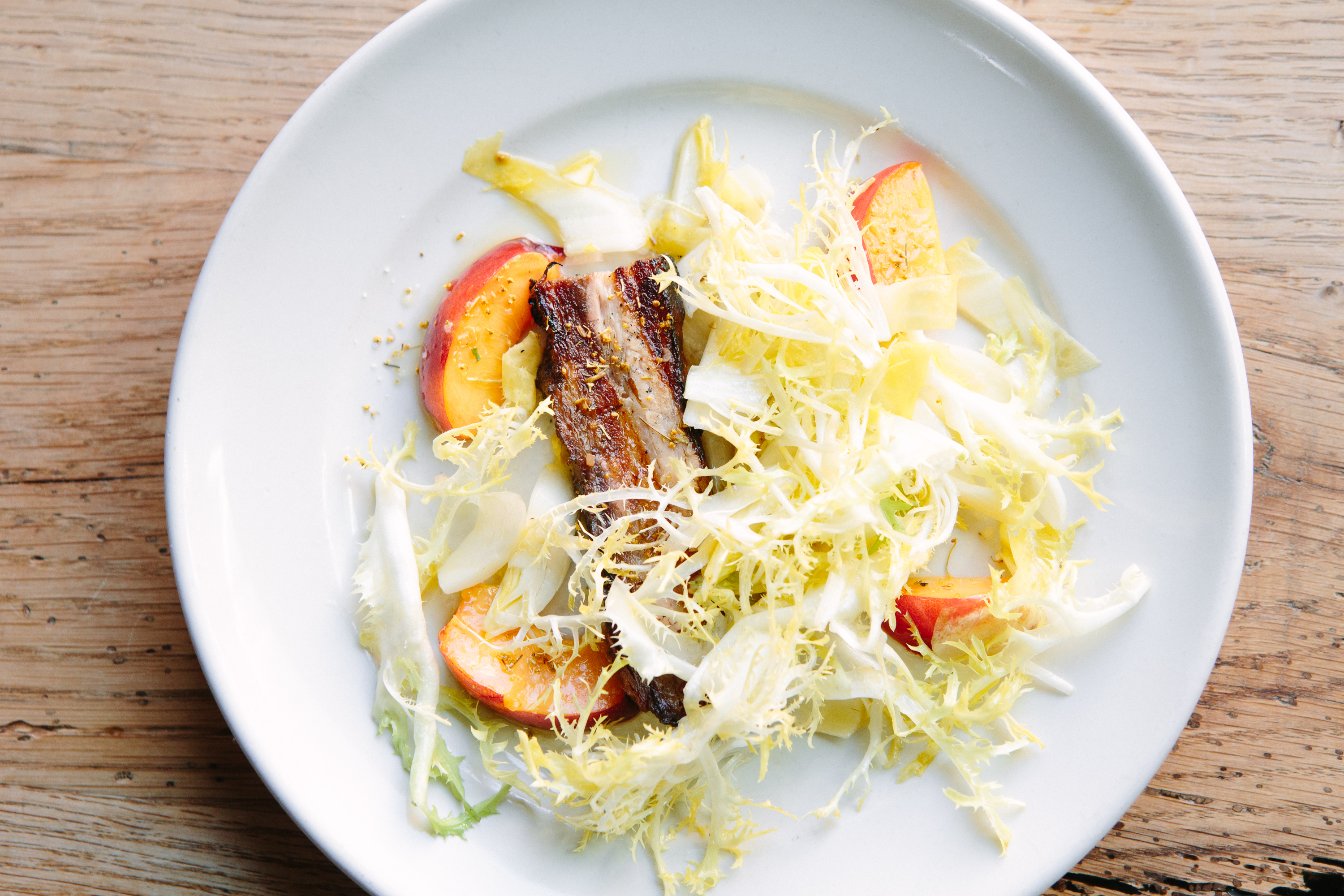 Roast Pork Belly with Nectarines, Frisée and Endive at Bar Agricole