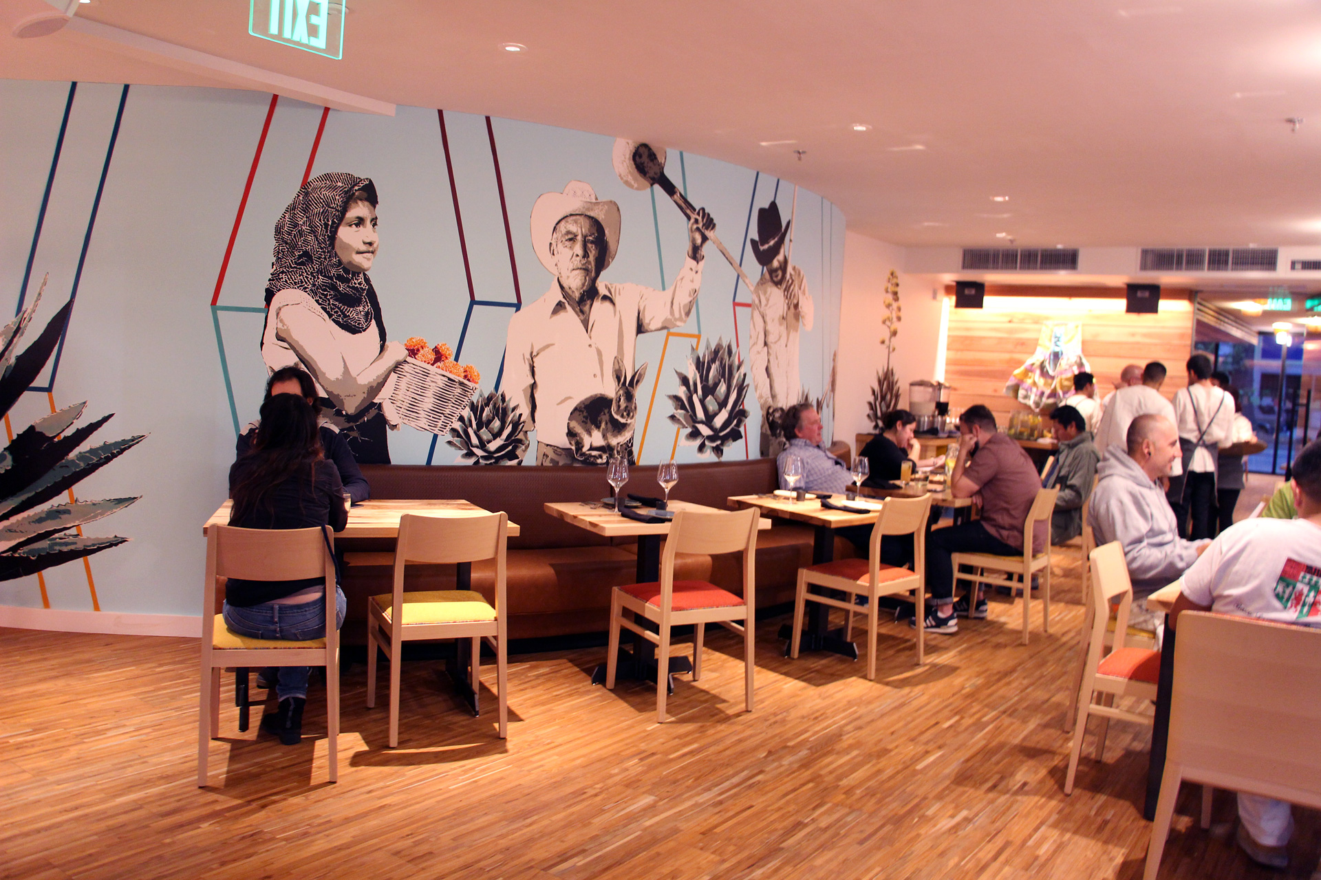 Agave Uptown interior with mural that represents the different parts of Oaxaca.