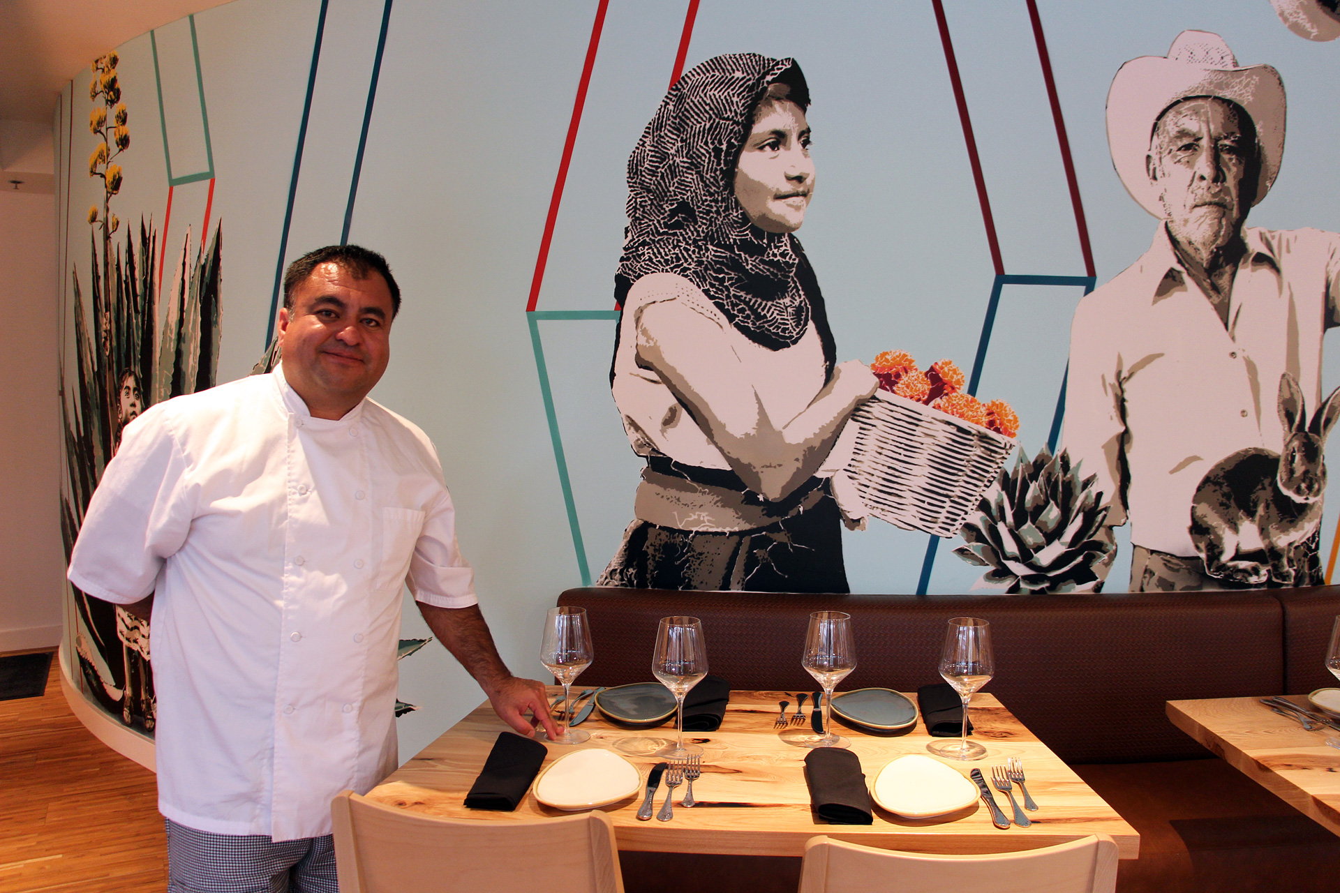 Chef Octavio Diaz in front of the mural at Agave Uptown