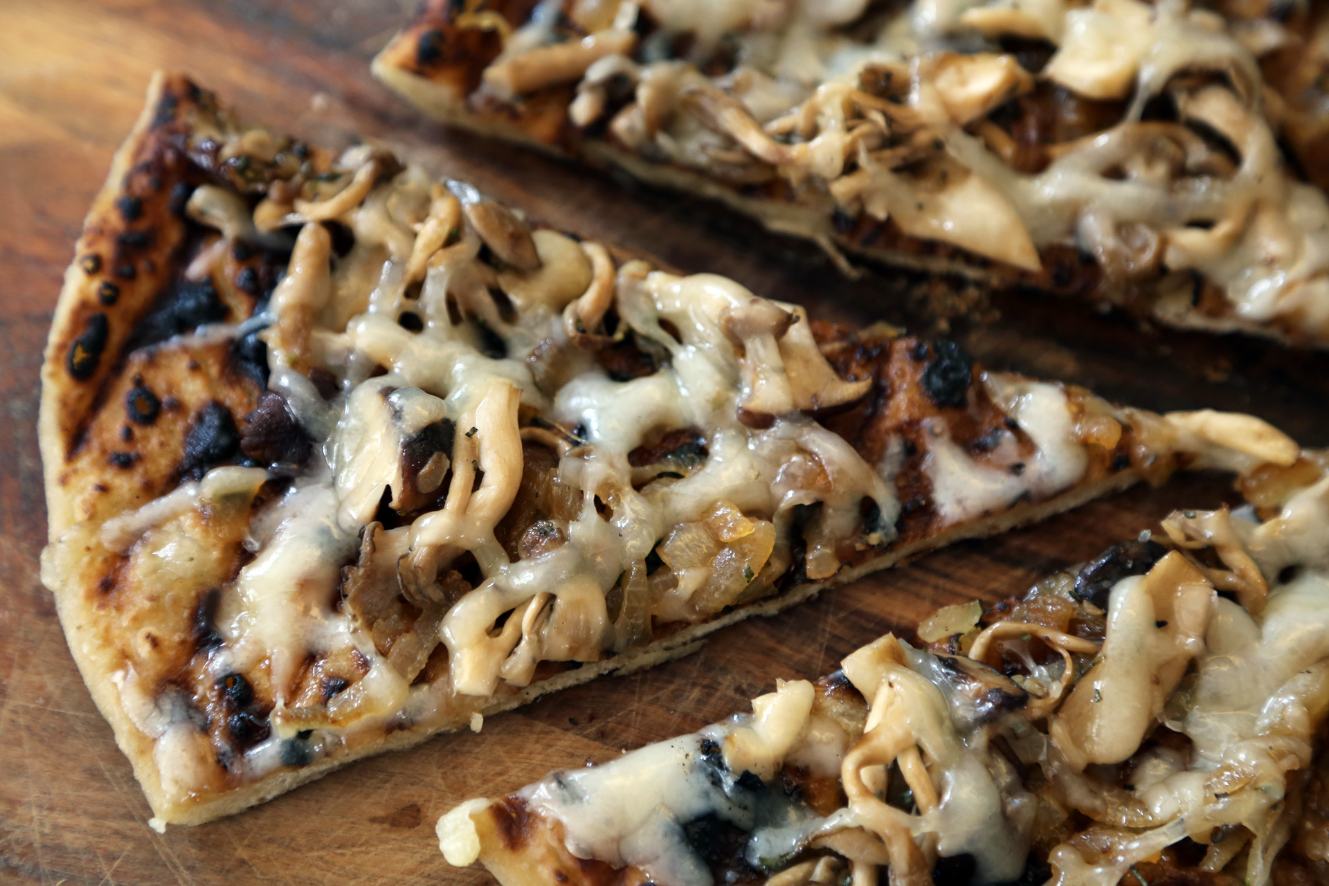 Grilled pizza with wild mushrooms, caramelized onions, and fontina