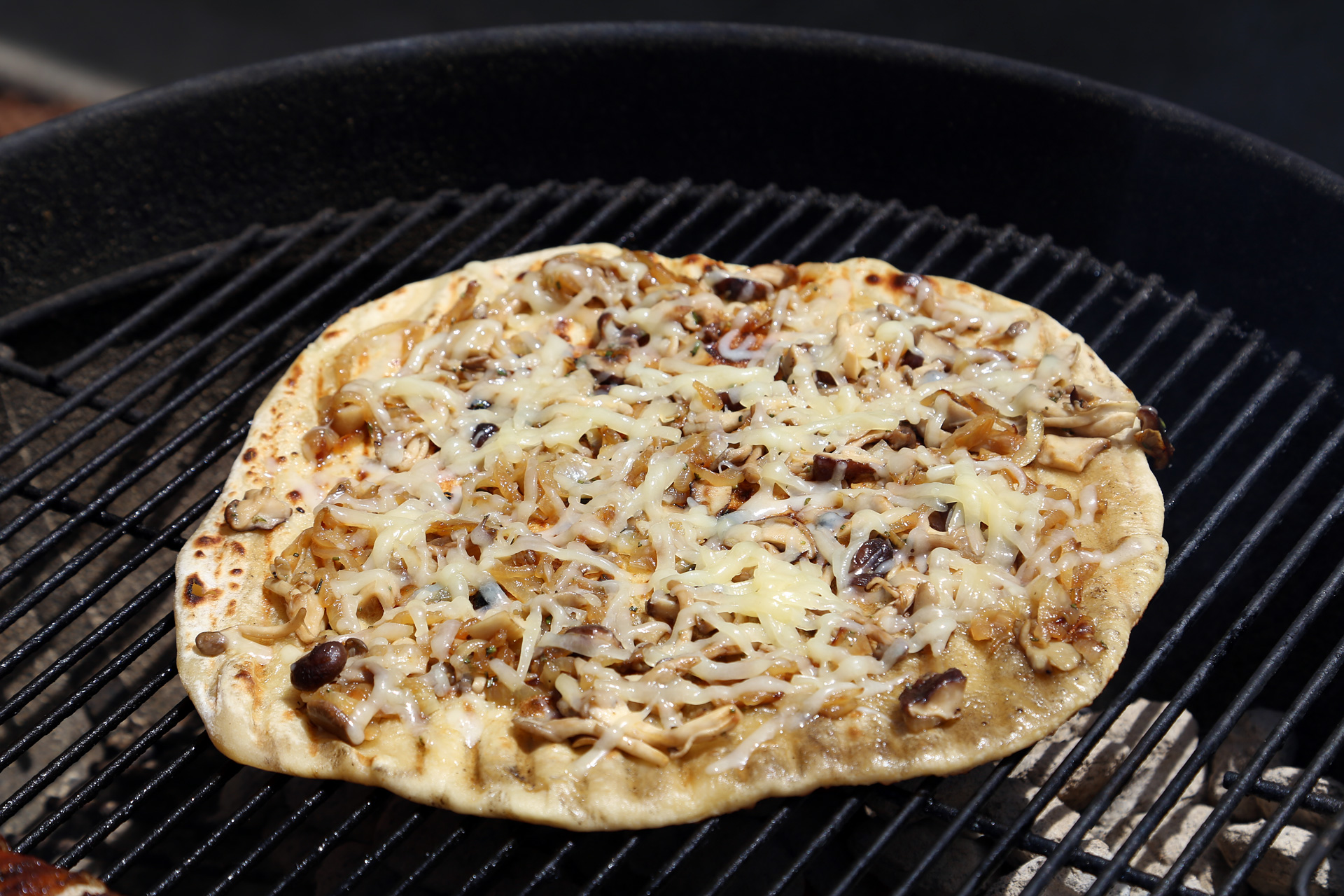 Cover the grill and let cook until the cheese is melted and bubbly and the dough is cooked through, rotating the pizza every so often to avoid hot spots and burnt pizza.