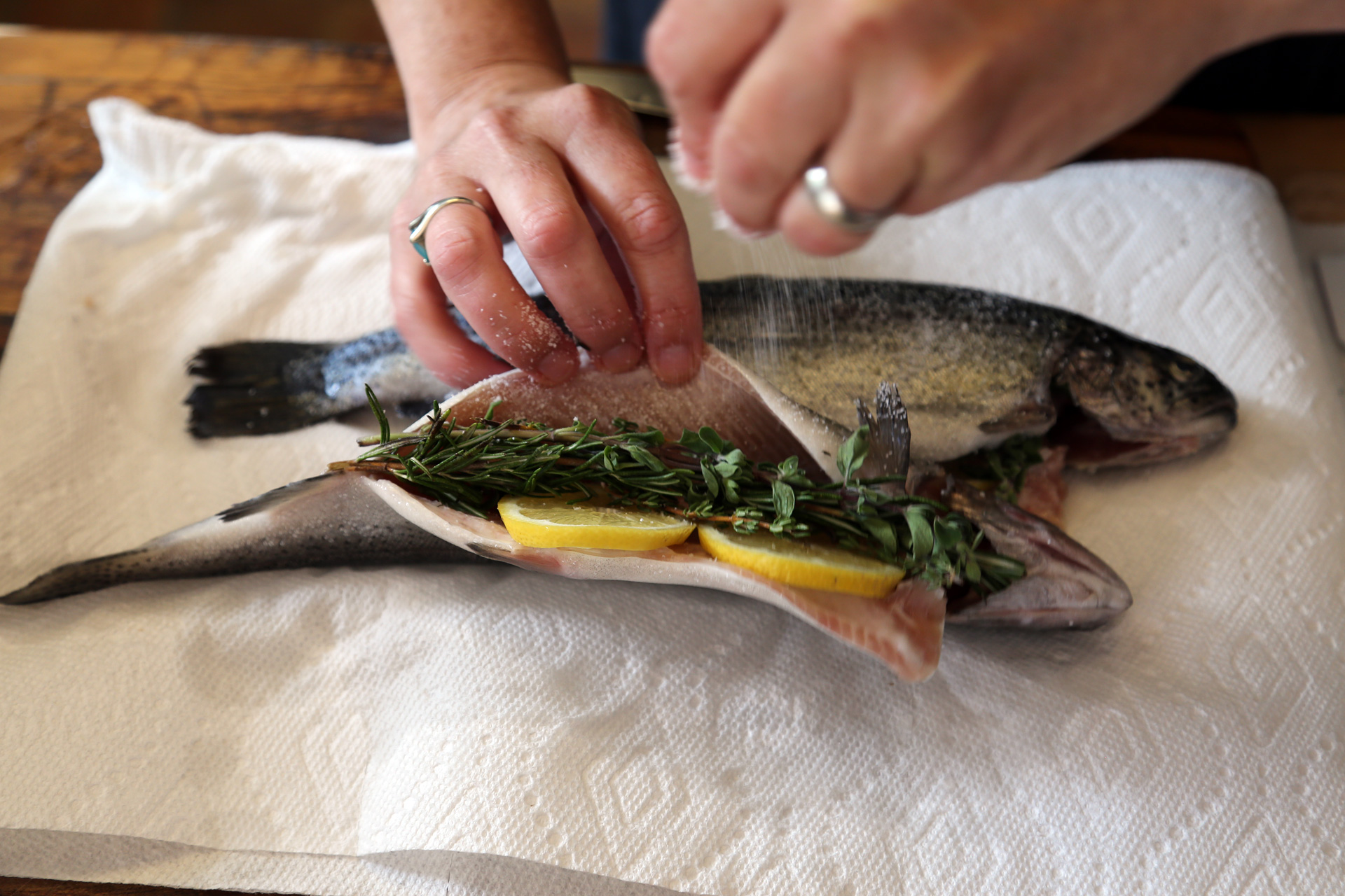 Sprinkle the cavity of each trout with salt. Stuff each trout with lemon slices and herb sprigs.