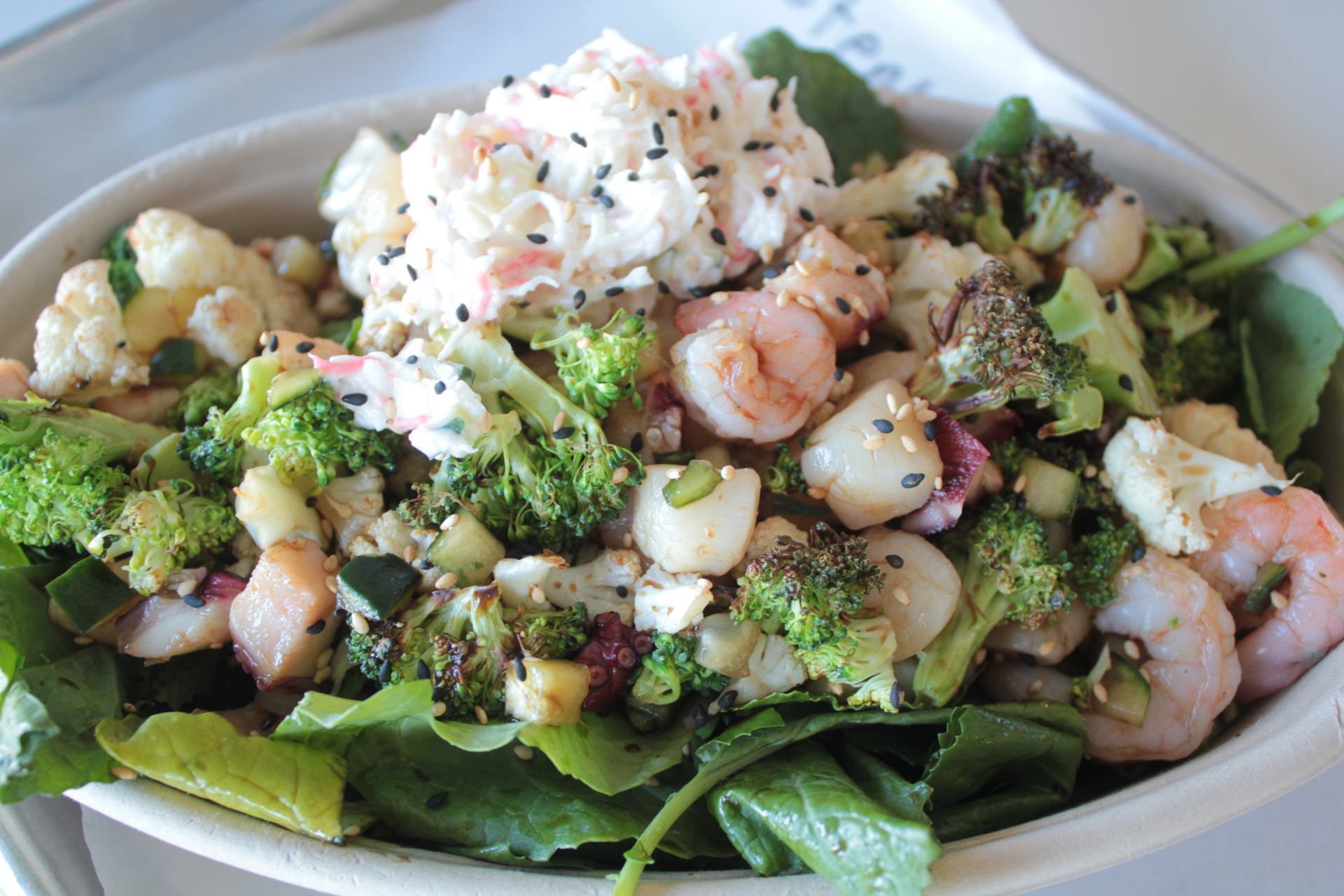 Scallops, octopus and shrimp in shoyu dressing over kale and roasted vegetables.