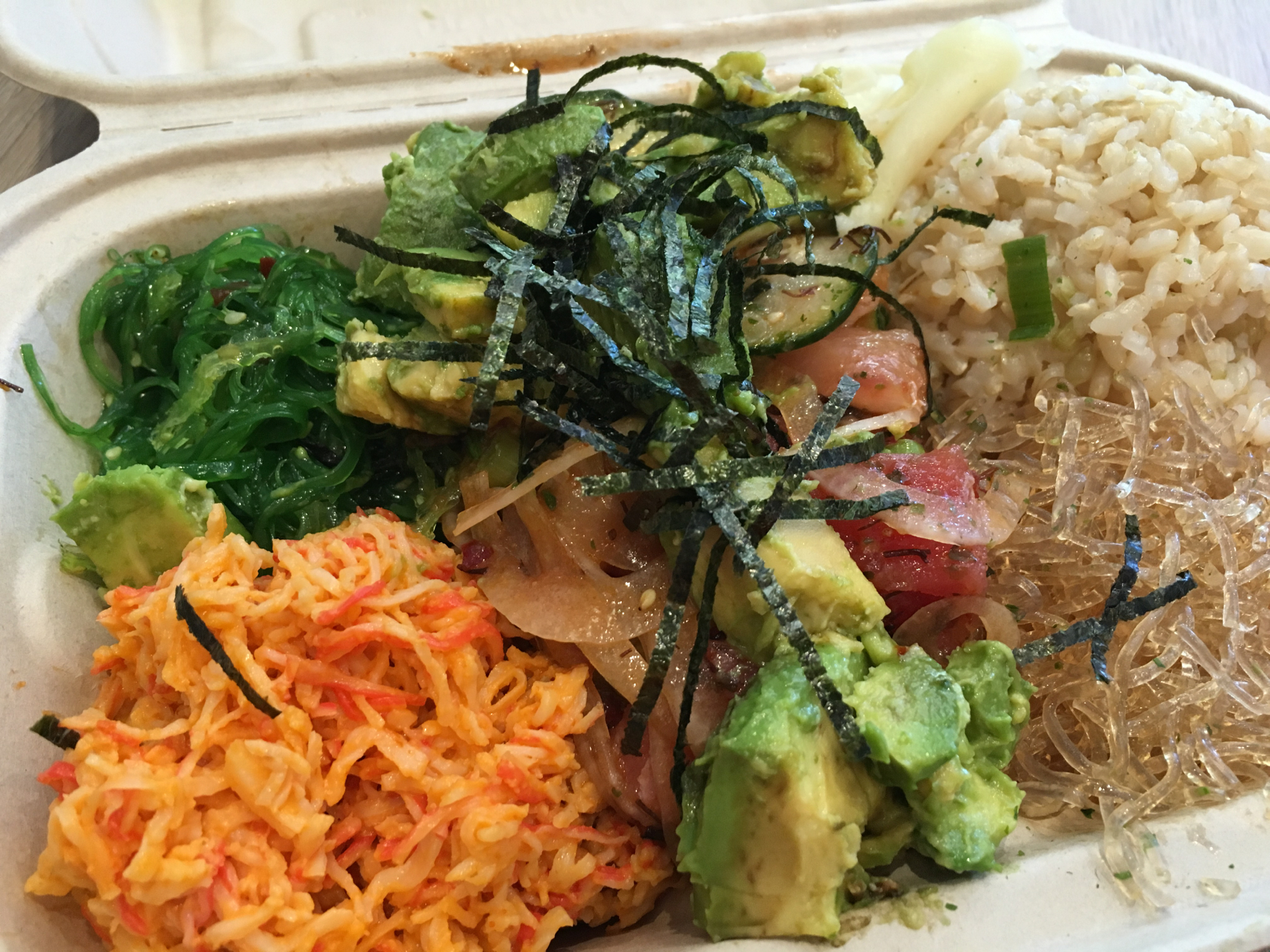 Ahi tuna over kelp noodles and brown rice with spicy crab salad and seaweed salad.