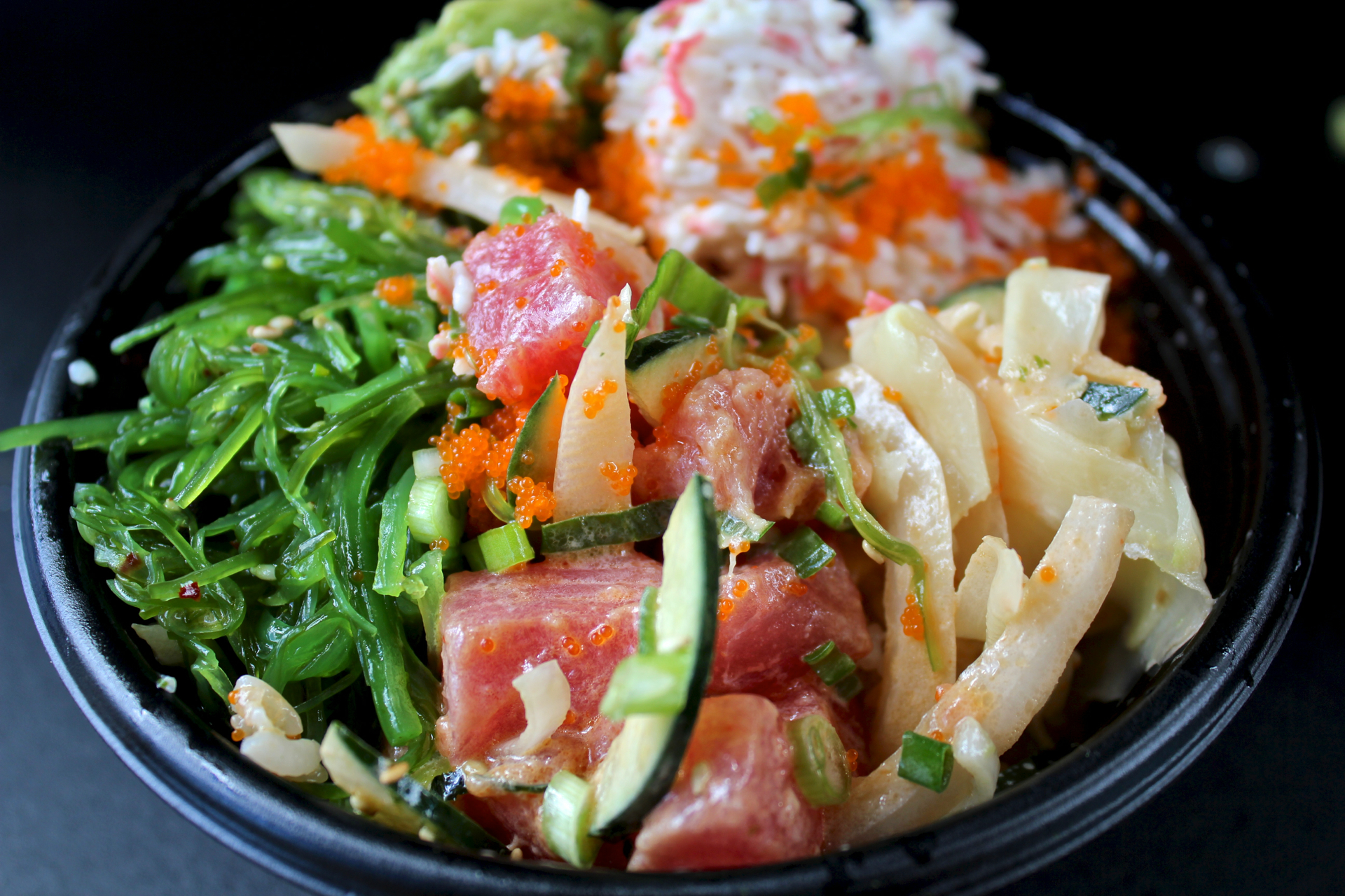 Ahi tuna and salmon with seaweed salad, ginger, cucumbers and green onions at Poki Bowl.