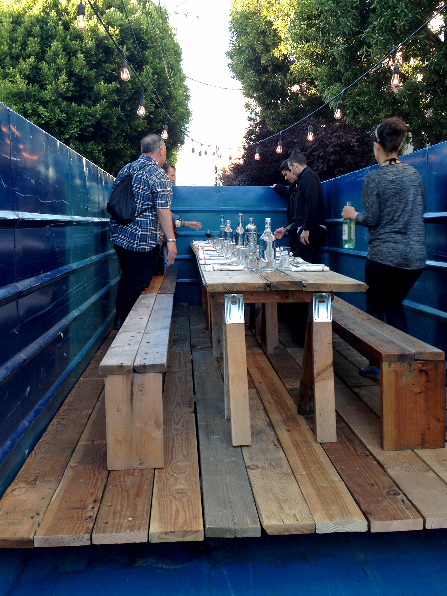 This San Francisco dumpster was decorated with glass tea lights, long wooden benches and bar towel napkins for the Salvage Supperclub dinner.