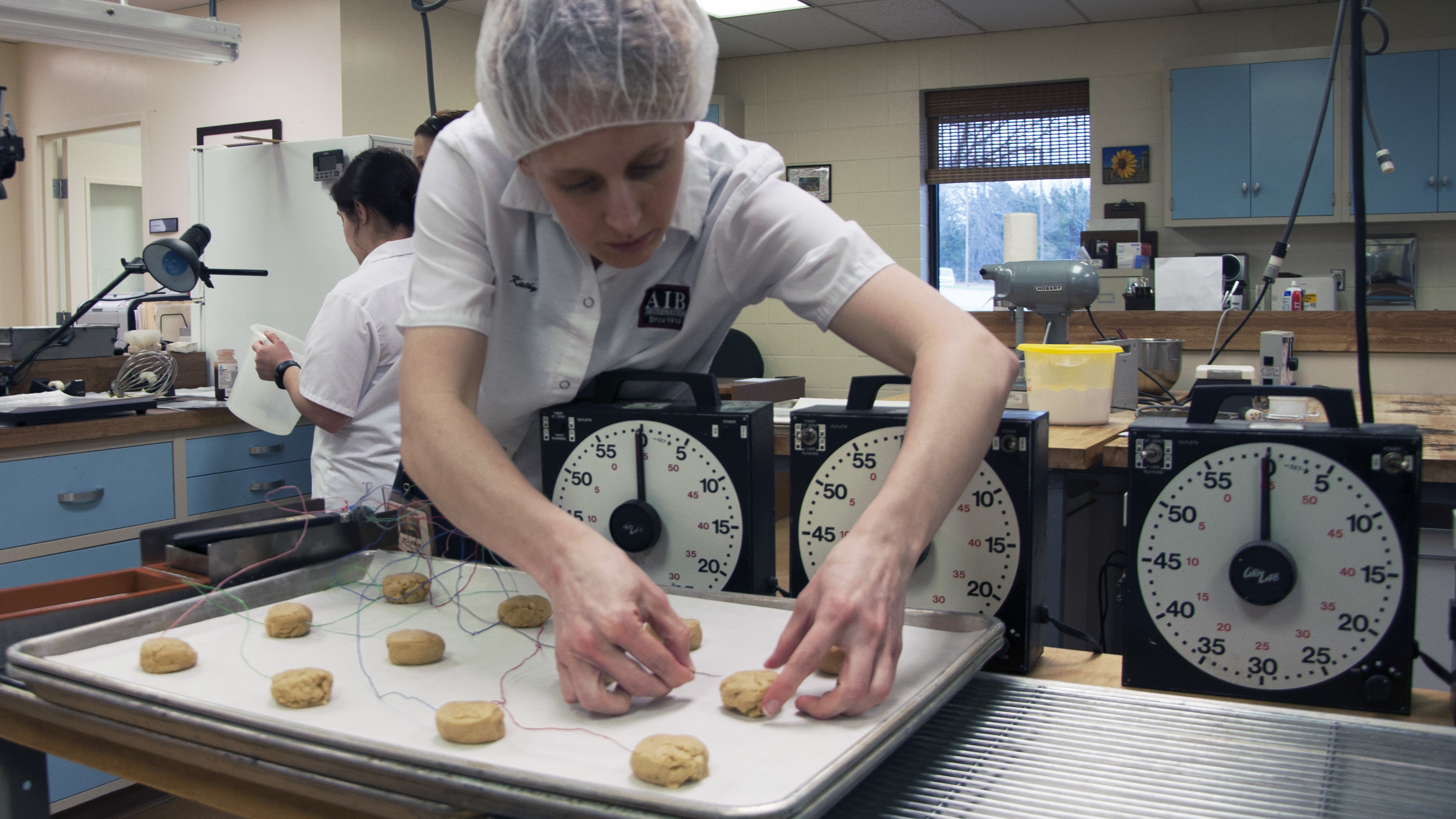 A researcher at AIB International inserts thermometers into cookie dough to monitor the baking temperature. The goal is to make sure the dough reaches the temperature needed to kill any bacteria inside.