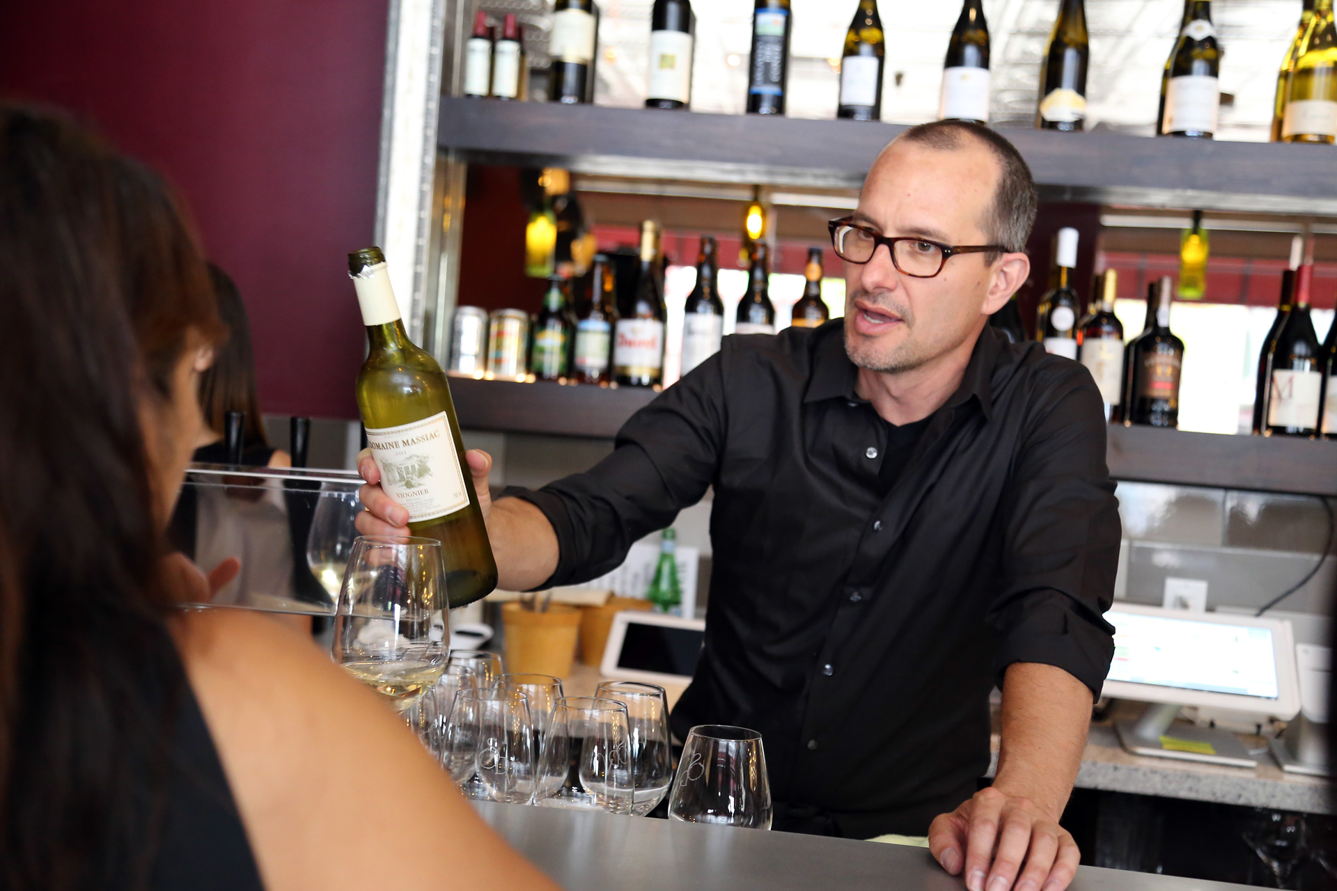 Wine Therapist and Educator, Joel S. Bachar, serves serving wine at the bar at Scopo Divino