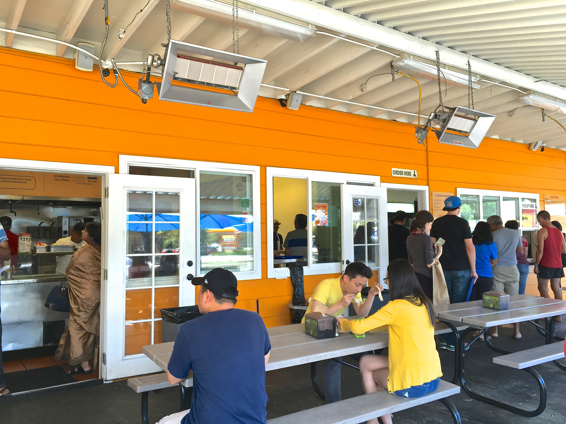 Customers wait on line to pickup their order from the kitchen at Falafel Stop in Sunnyvale.