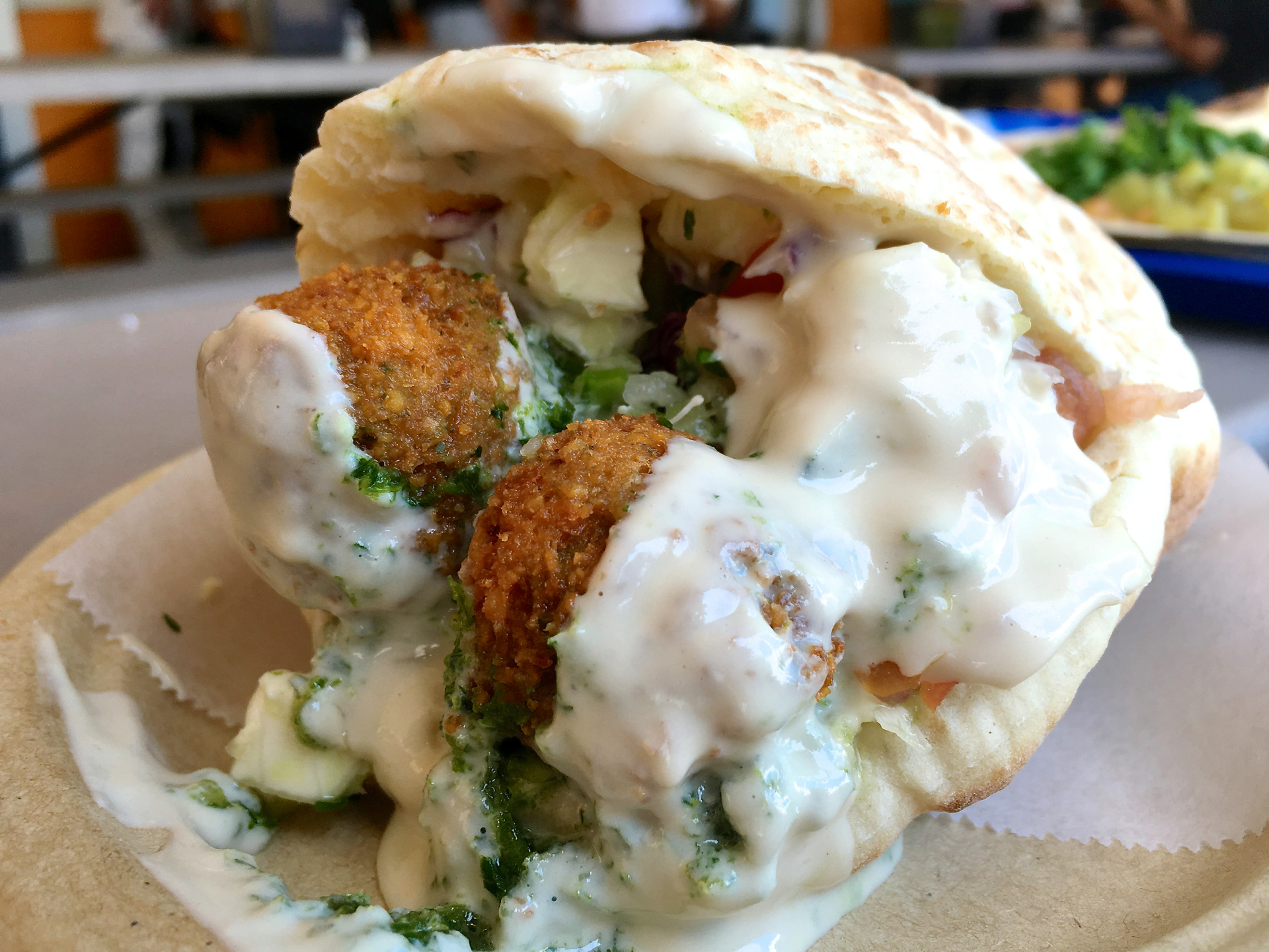 A falafel pita with spicy tahini at Falafel stop.