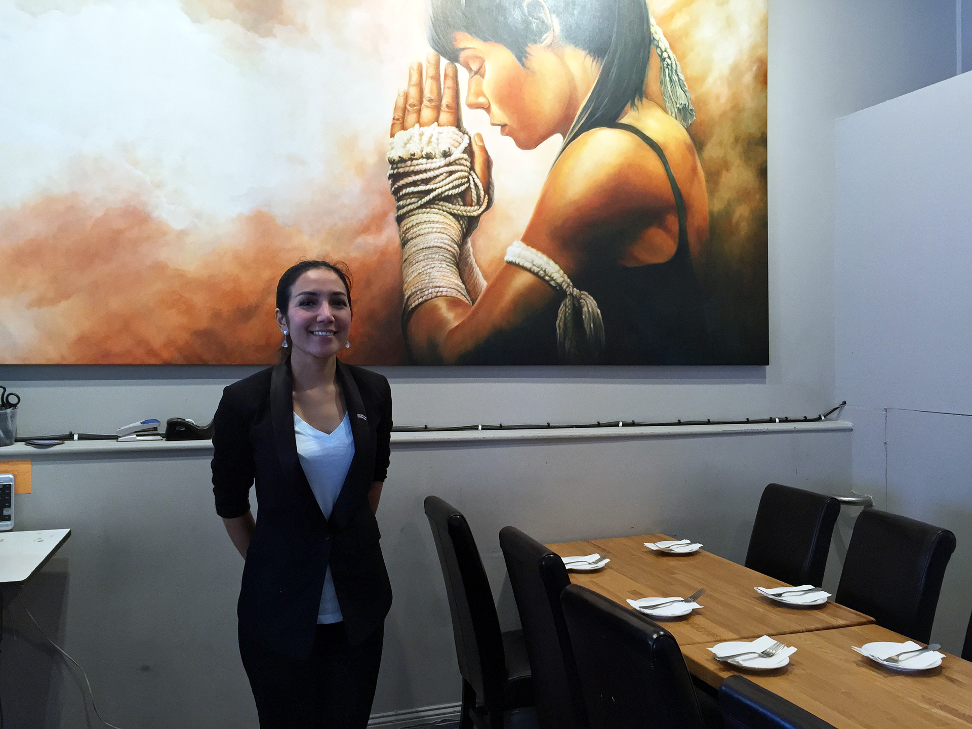 Chef-owner Salisa Skinner with one of her sister Air's large oil paintings.