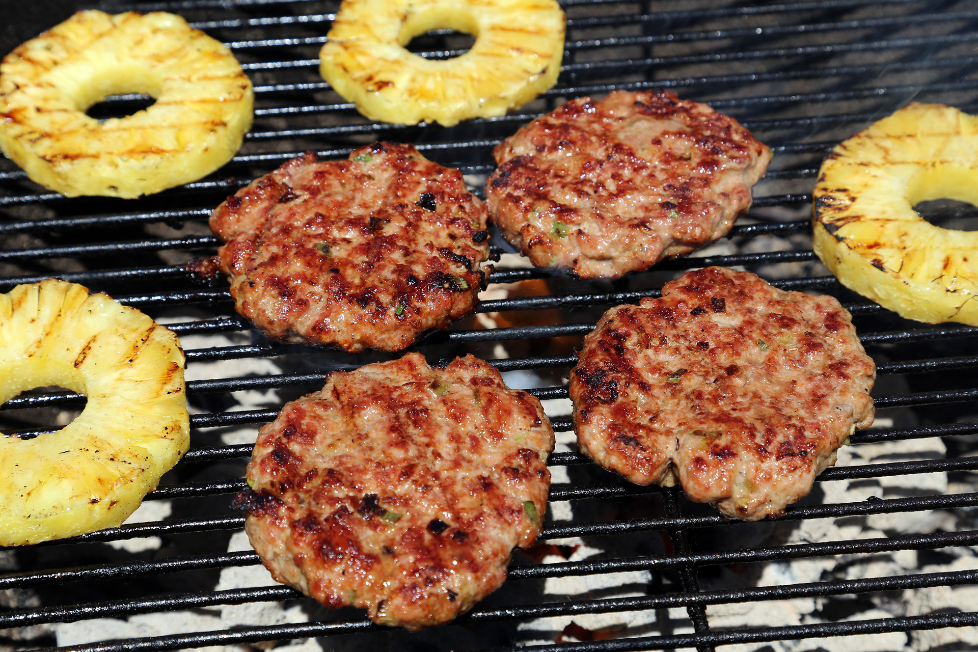 Grill the patties over the fire until nicely seared on both sides, turning occasionally, about 4 minutes on each side. During the last 4 minutes of cooking, add the pineapple slices. Grill, turning once, until nicely seared.
